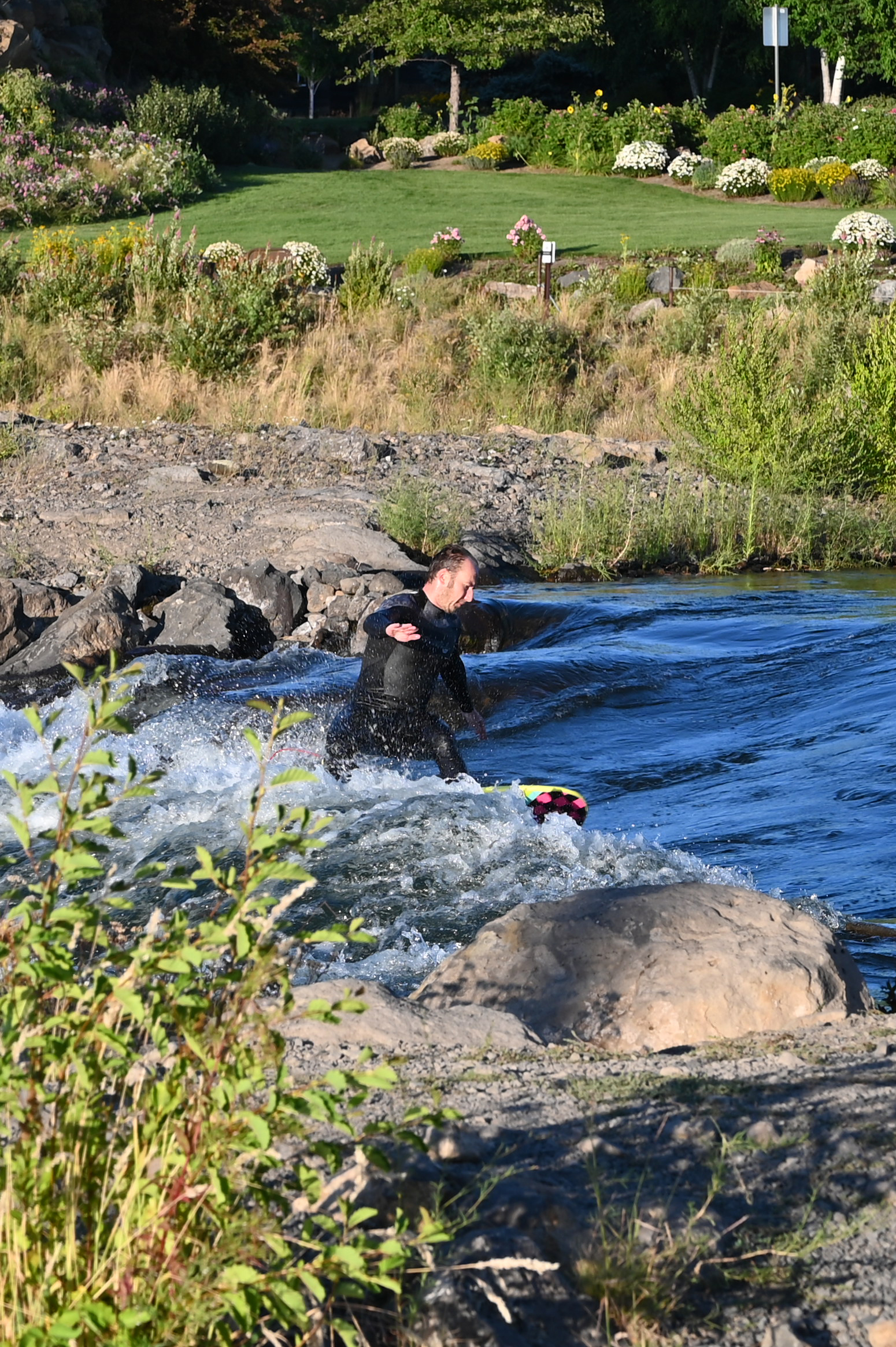 surfer cutting a turn on deschutes river standing wave in bend