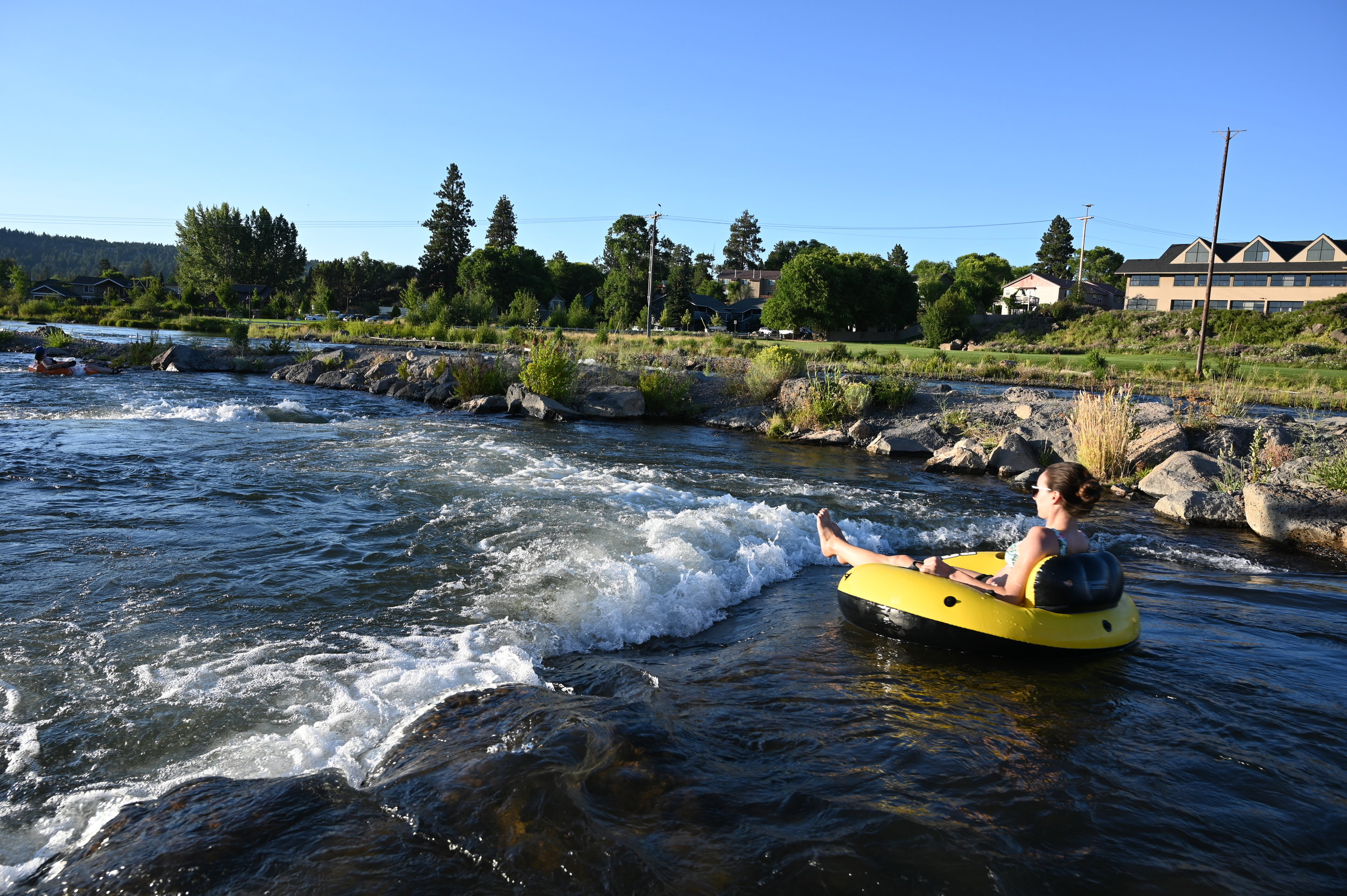 tubing person floats through whitewater park on clear day