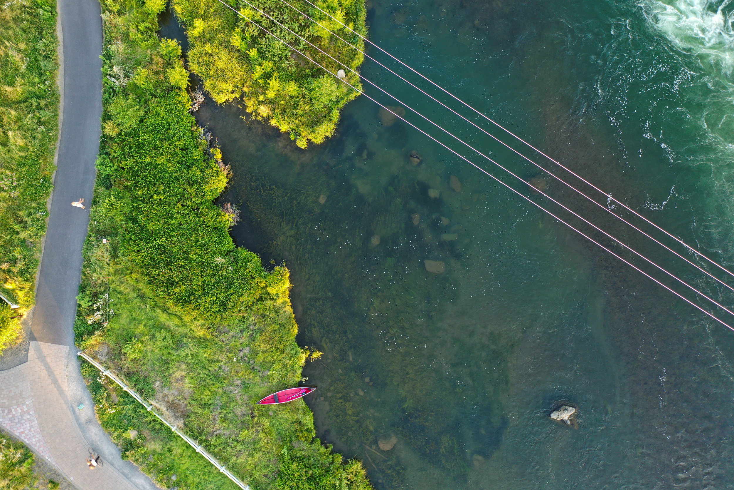 aerial view of a red kayak on the shore of a river