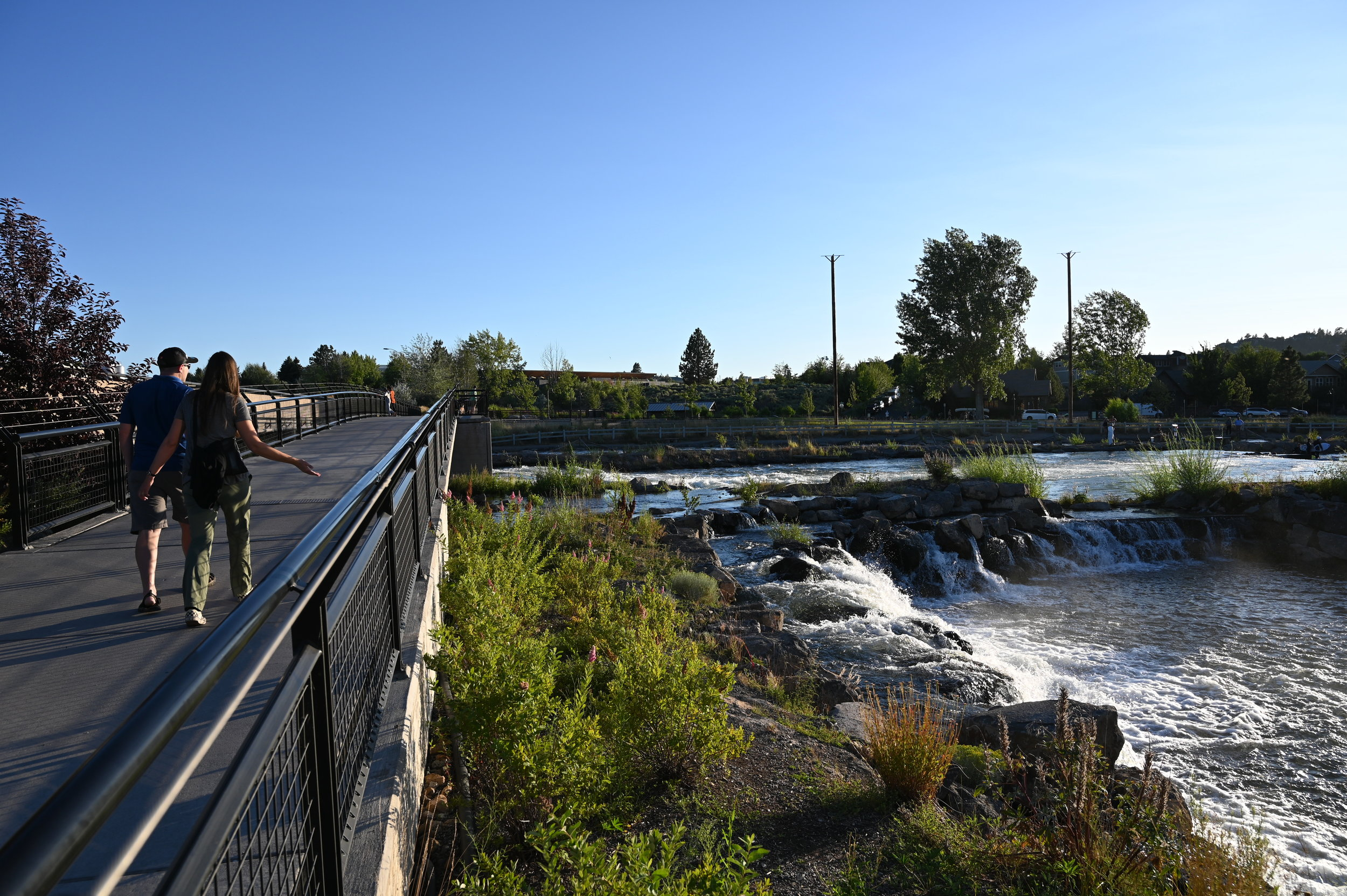 people cross pedestrian bridge over deschutes river at sunset