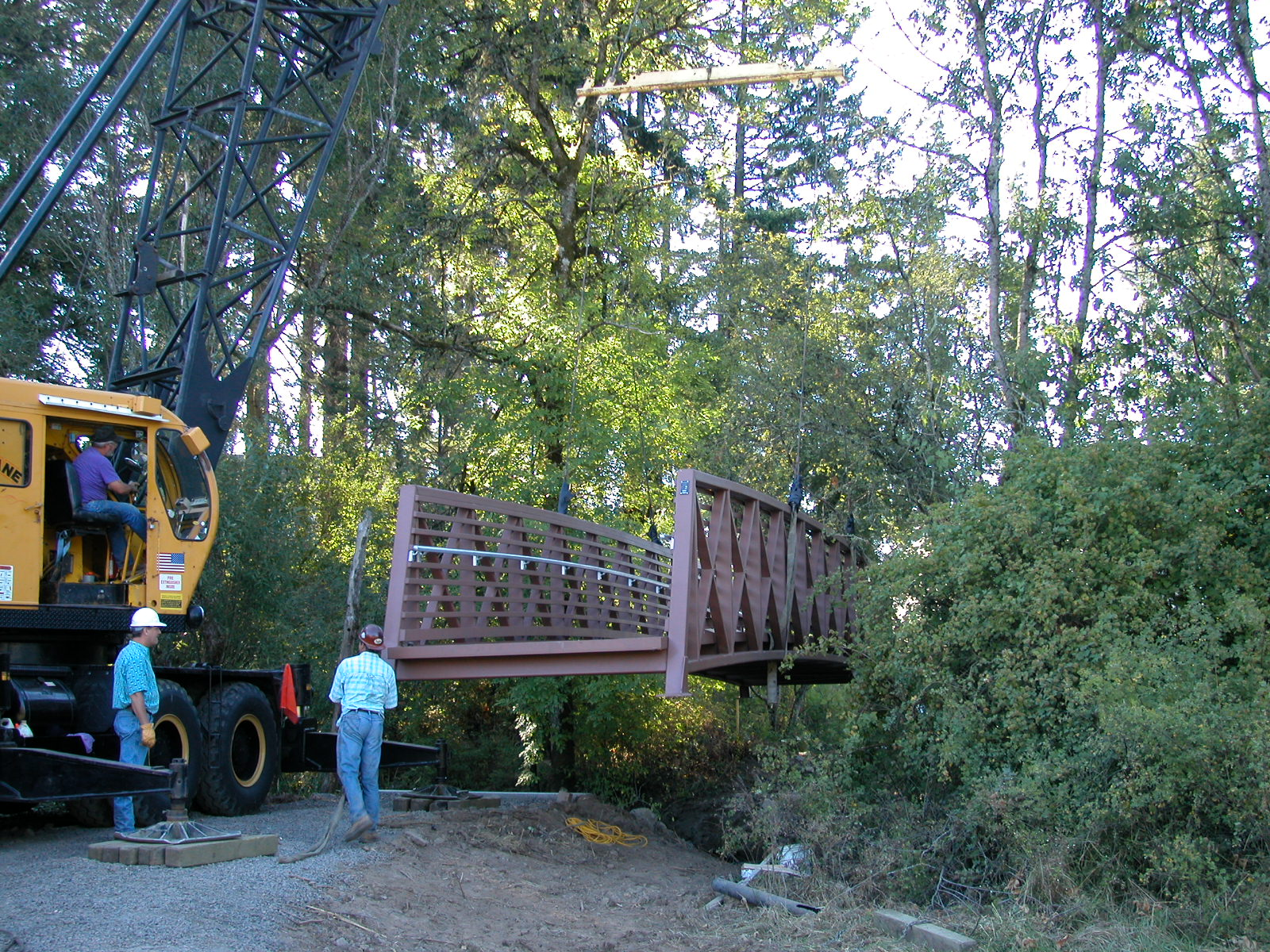 crane delivering trail bridge with workers and a forest around