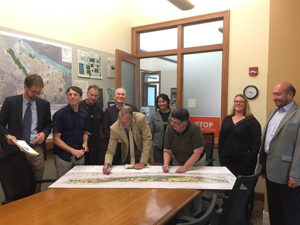 Portland City Commissioner Nick Fish signing plans for Gateway Green, alongside project champion Linda Robinson