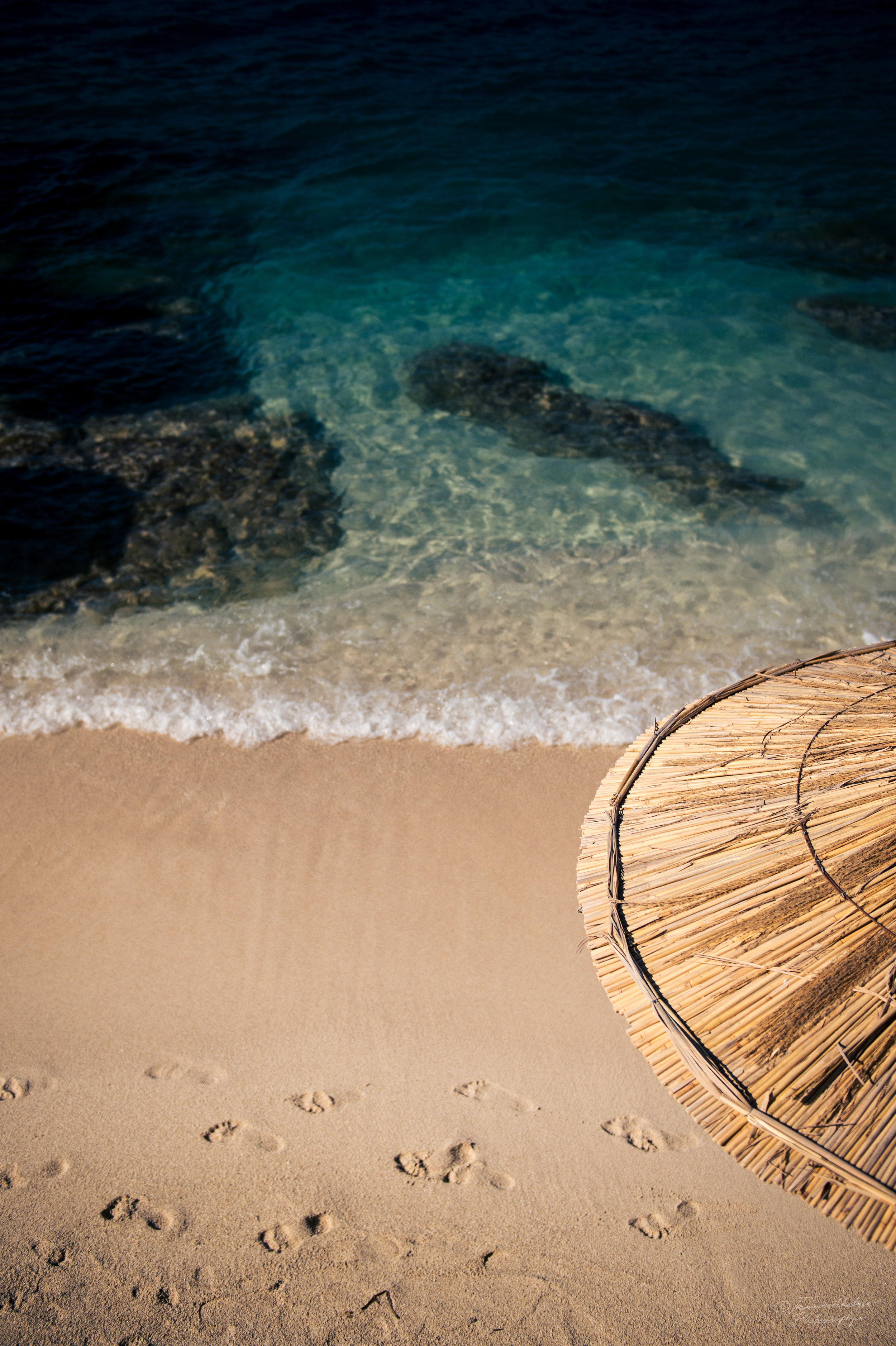Footprints in the sand and a parasol on a beach.jpg