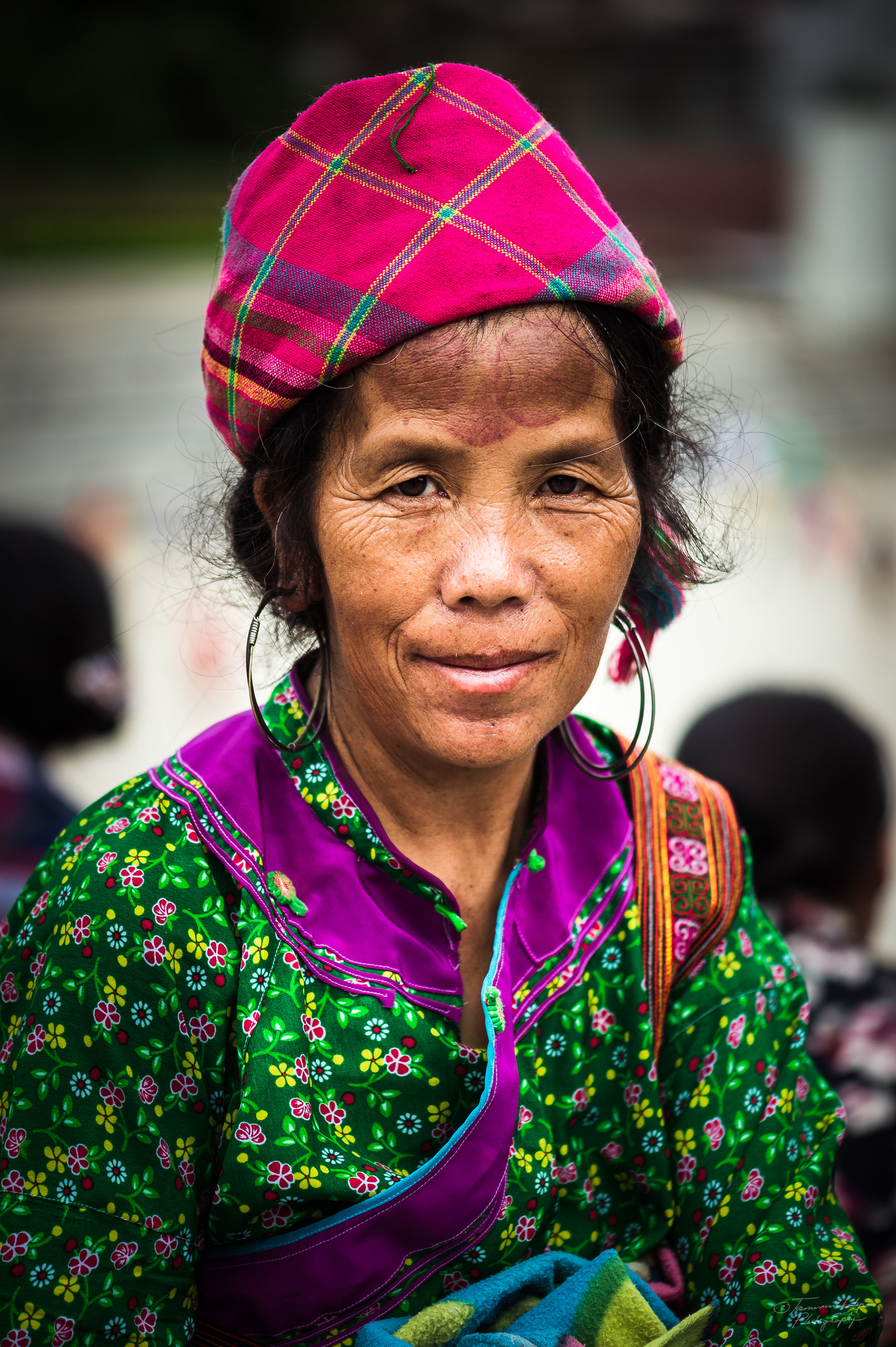 A H´mong woman in the market in Sapa town. Black marks in her forehead come from a traditional pain relief. For a headache a buffalo horn´s stub is heated and then pressed on forehead. The mark comes off in days or weeks.