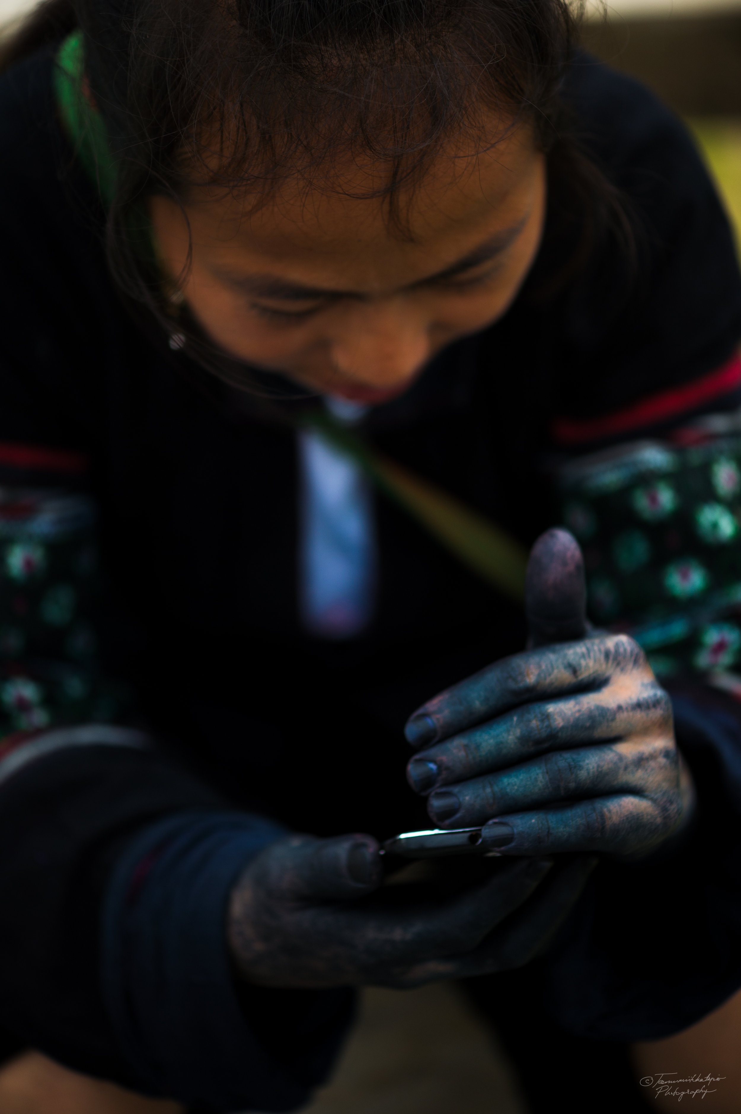 A young H´mong woman checks her phone in the market. H´mongs traditionally dye their fabrics with natural colors they get from indigo plants. Dyeing fabrics makes their hands blue.