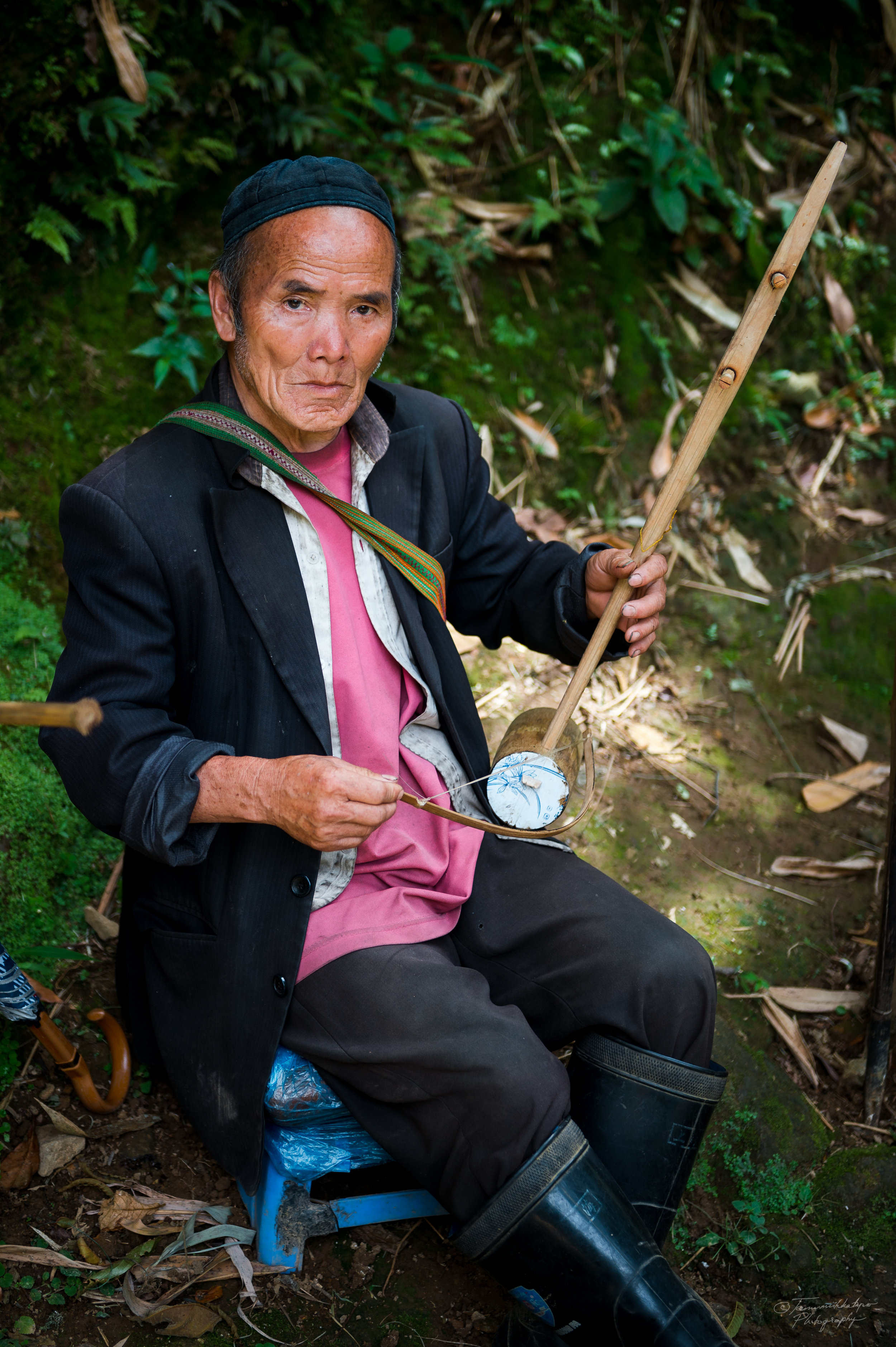 A man is playing a traditional two-stringed instrument called Dan ho