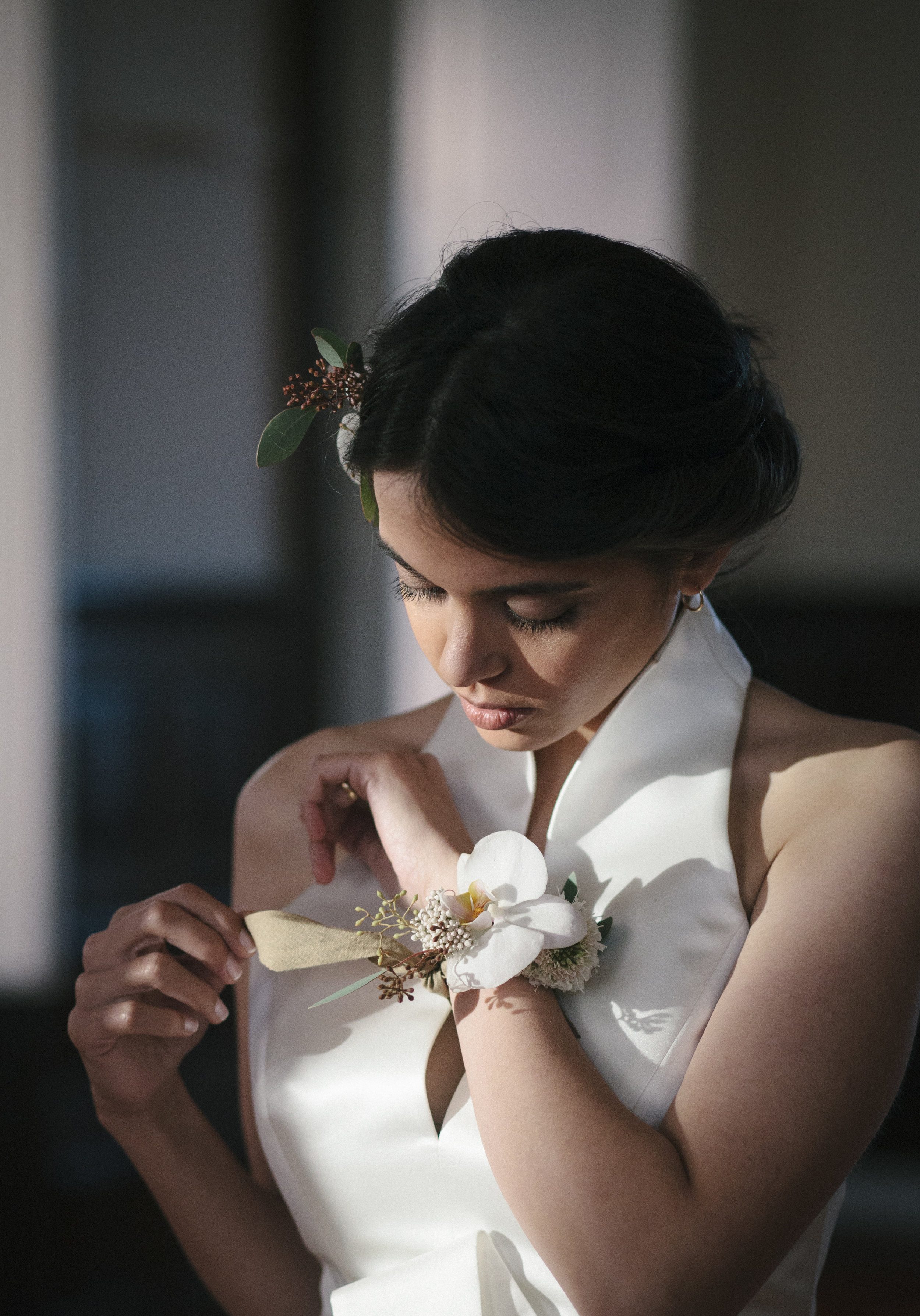Portrait of a bride wearing magnolia headdress and bracelet and an elegant, modern dress by Jesus Peiró Porto. Images by Julia Jardim and Joana Carvalho for Oceânica.