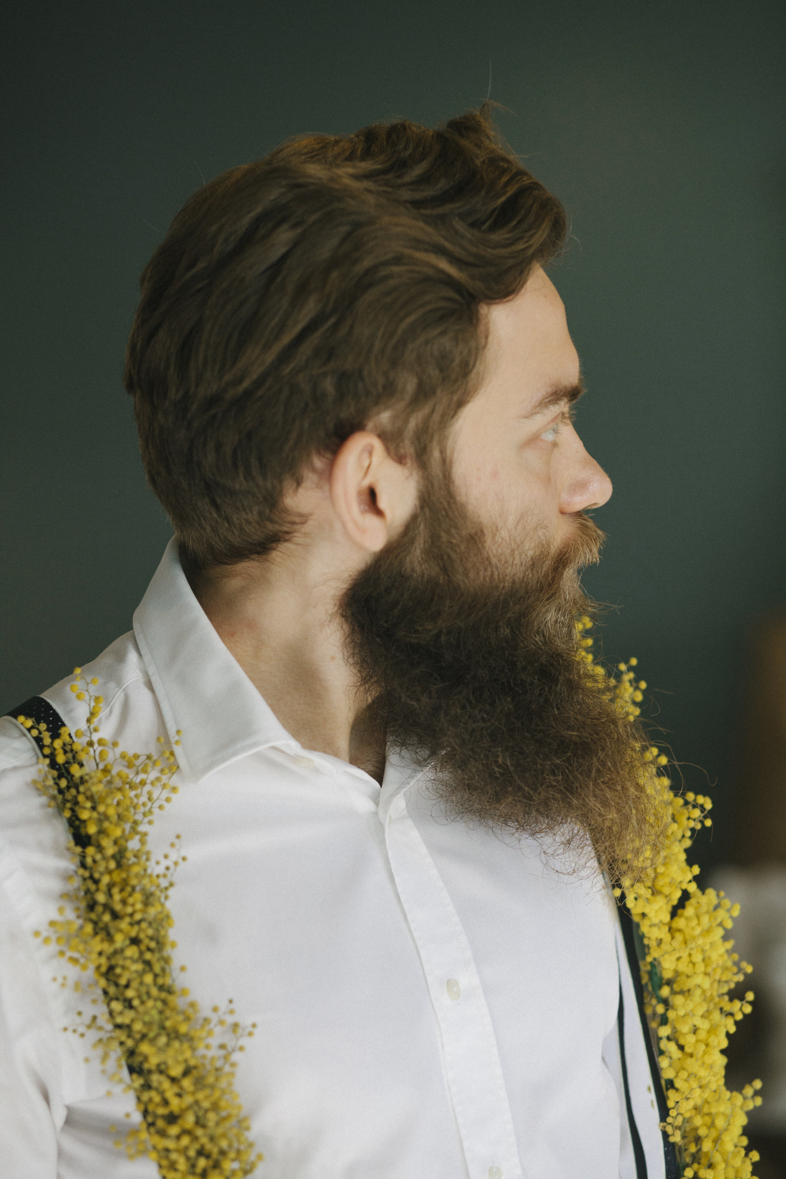 Portrait of a viking-looking groom wearing yellow-flower covered suspenders. Editorial shoot by Oceânica Photography in Portugal