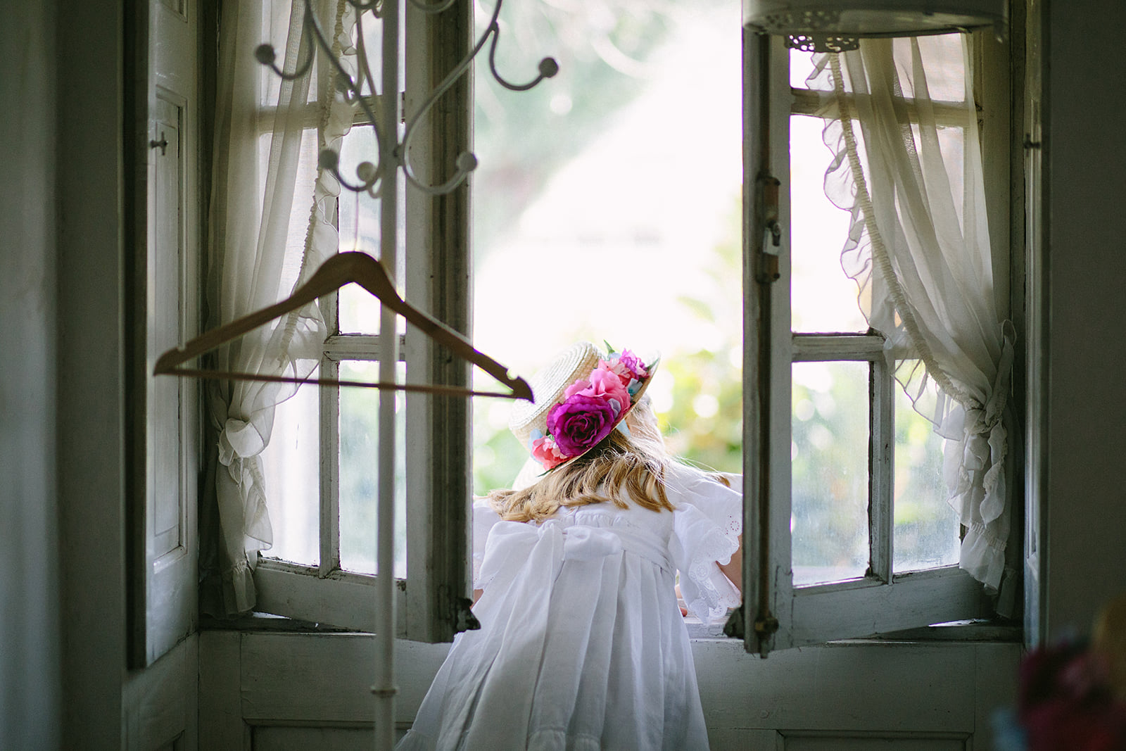 Flower girl in a flower hat looking out the window in a backyard wedding in Portugal.