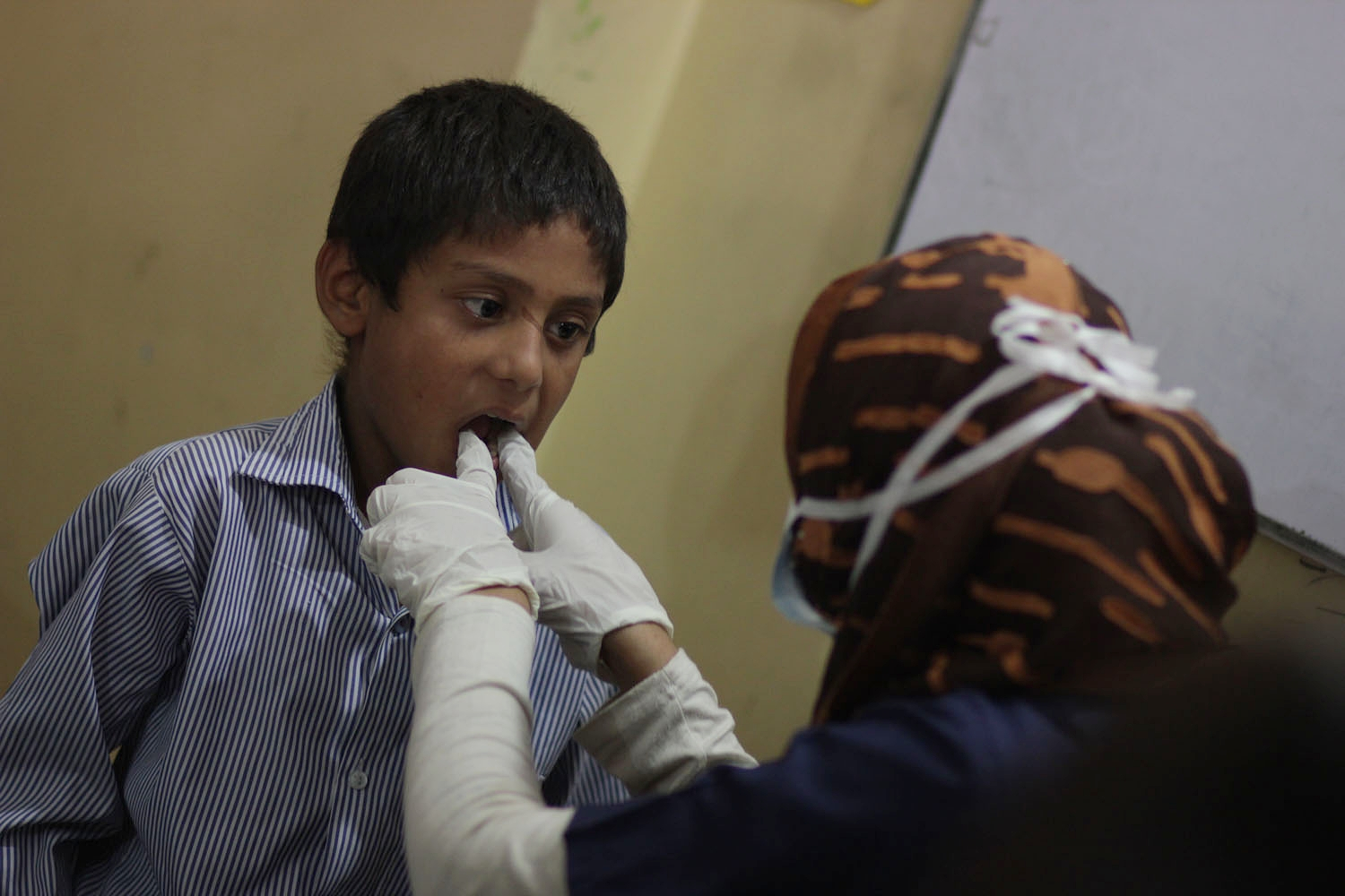 Dr. Razzak conducting an oral exam during Barkat's free health camp conducted at Rising Star School for underpriviledged children in Lahore.