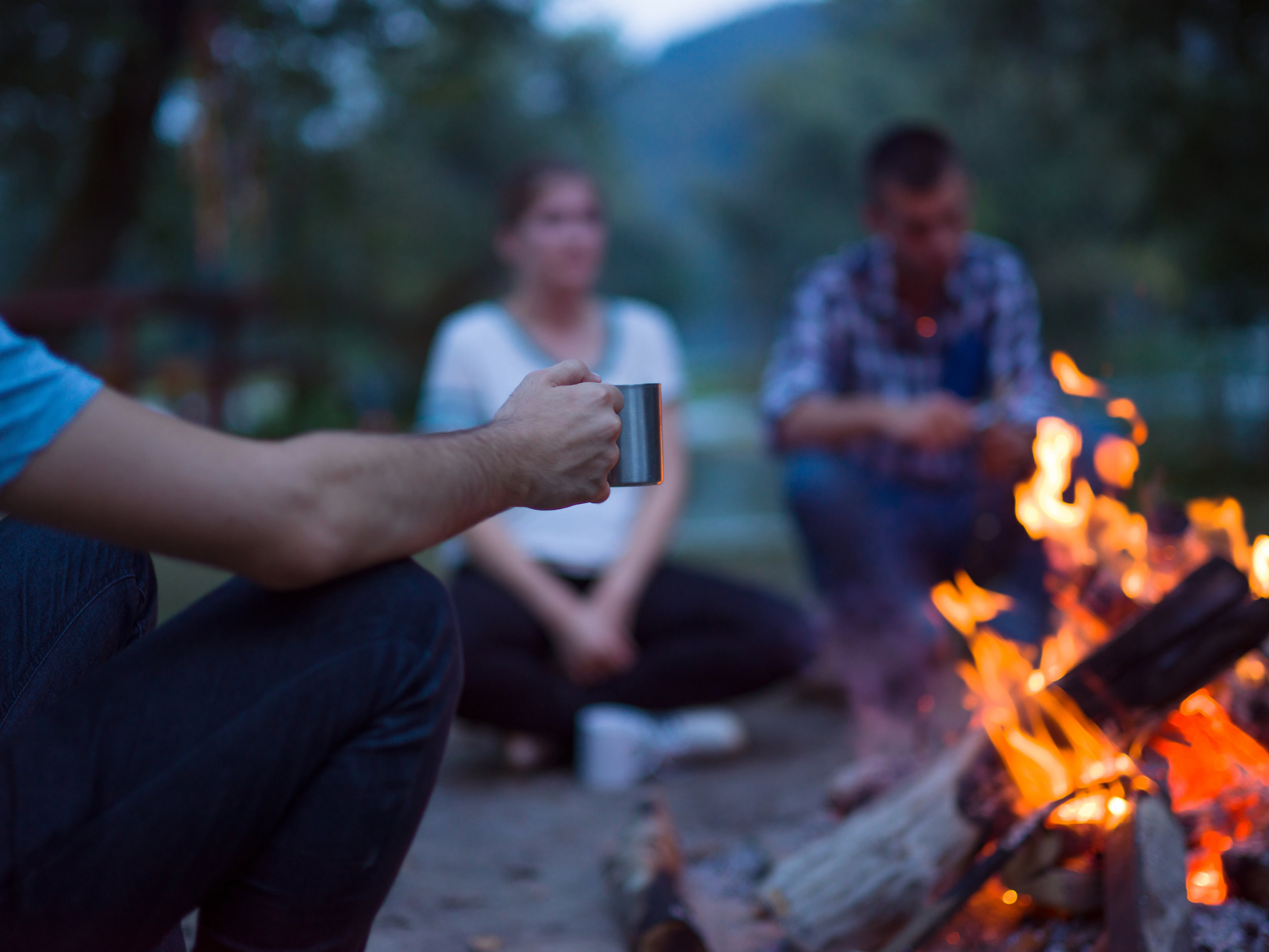 young-friends-relaxing-around-campfire-HJP84WR.JPG