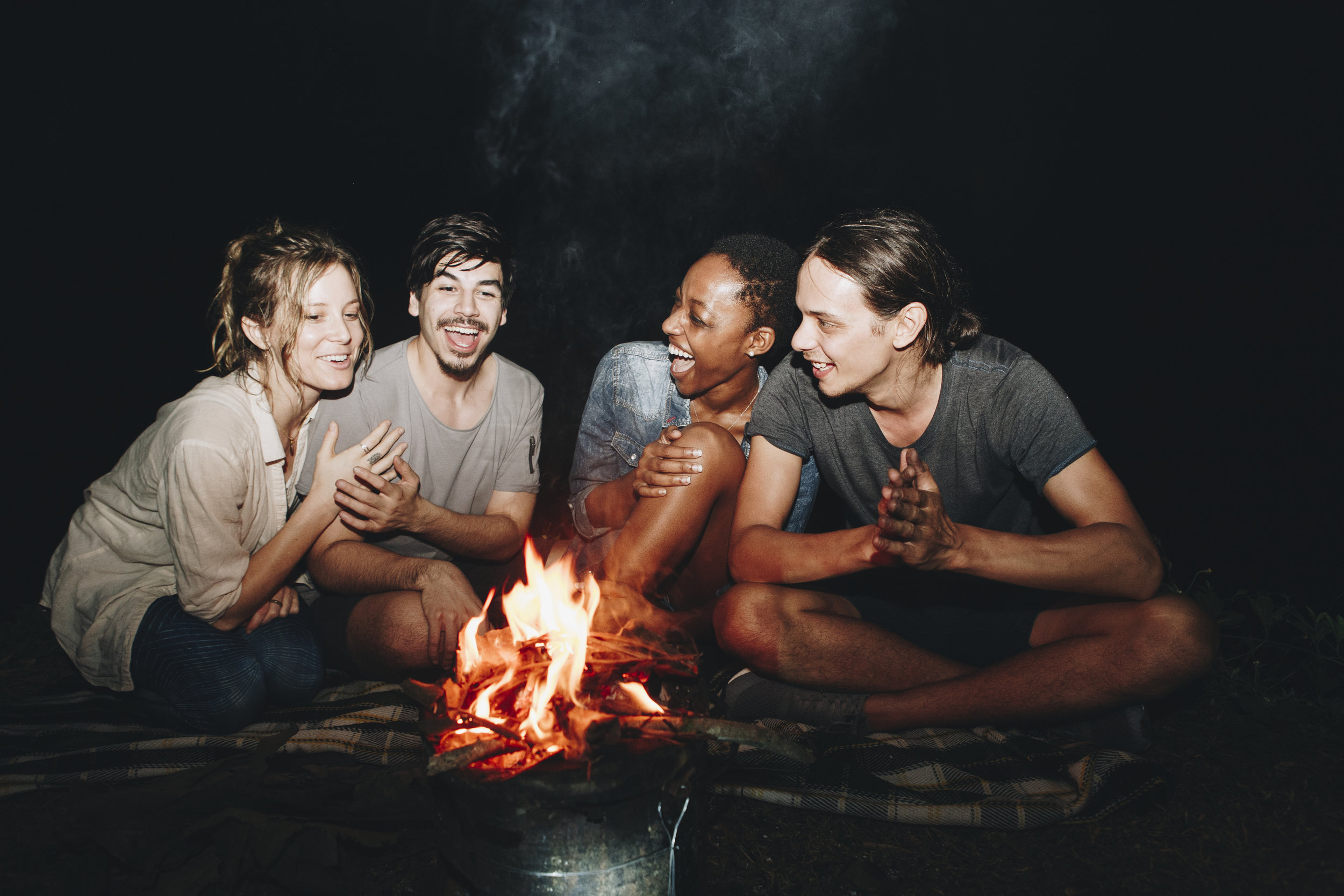 group-of-friends-sitting-around-a-bonfire-at-a-P87NQBA.jpg