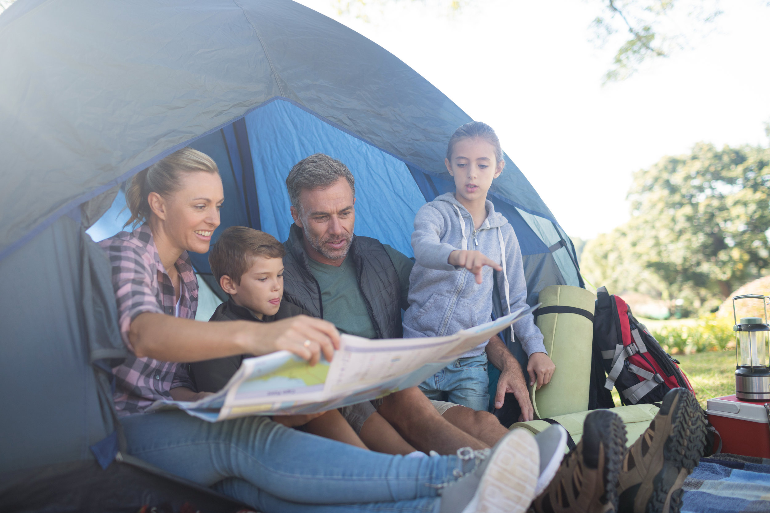 family-reading-the-map-in-tent-X3AKMUC.jpg