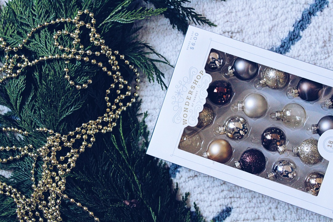 Christmas ornaments and gold beaded garland from Target and fresh garland on floor.
