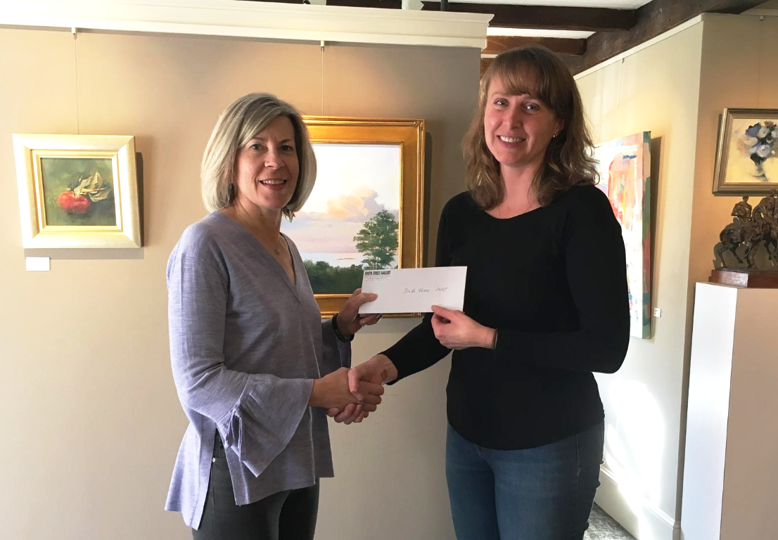 SNAP Board Member Donna Kearny accepts a donation of funds raised from Kate Sotolova, manager of South Street Gallery