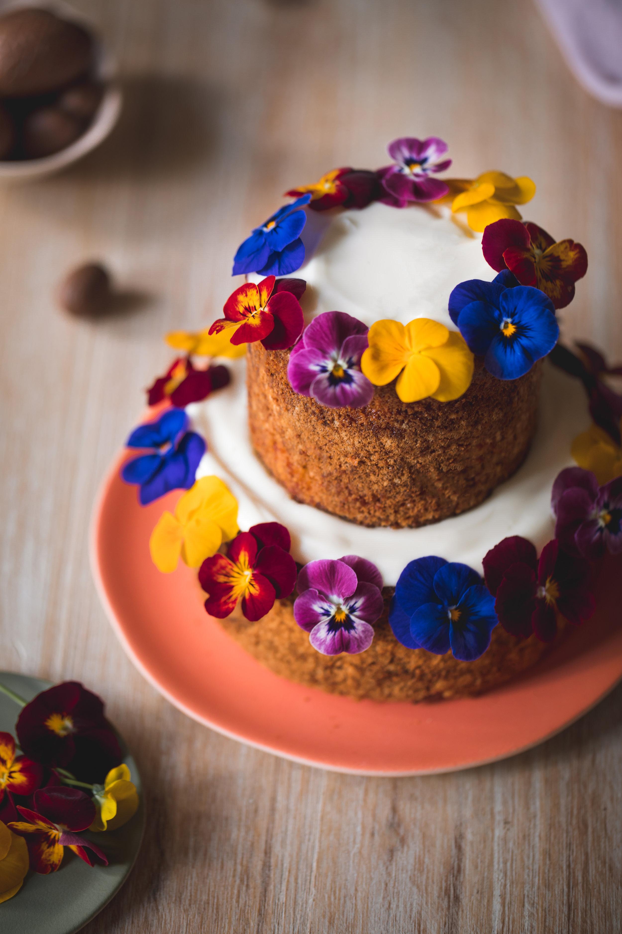 Gâteau à la carotte et aux noix de pecan décoré de fleurs comestibles