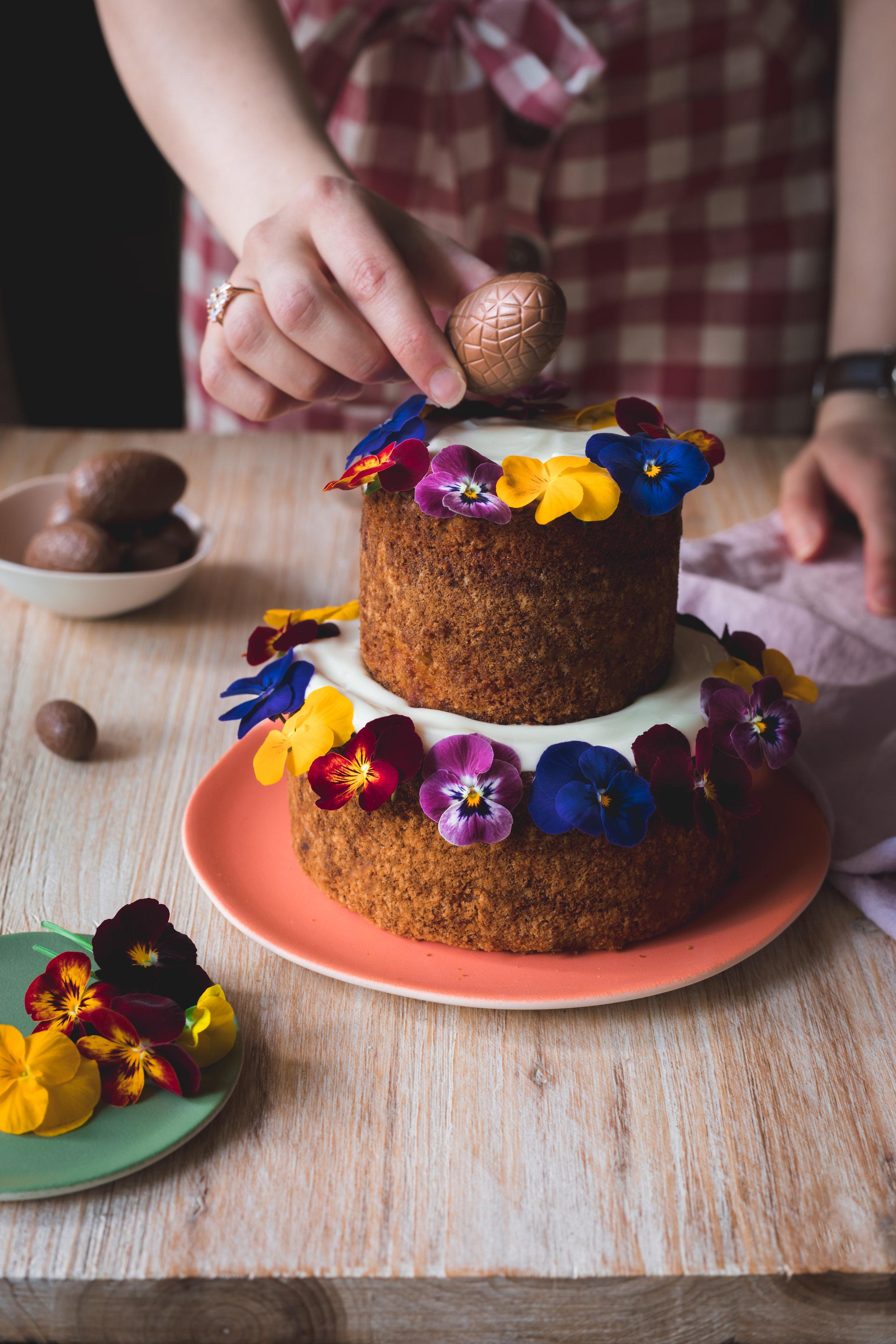 Une petite ambiance de Pâques en décorant le gâteau à la carotte et aux noix de pécan avec des oeufs en chocolat.