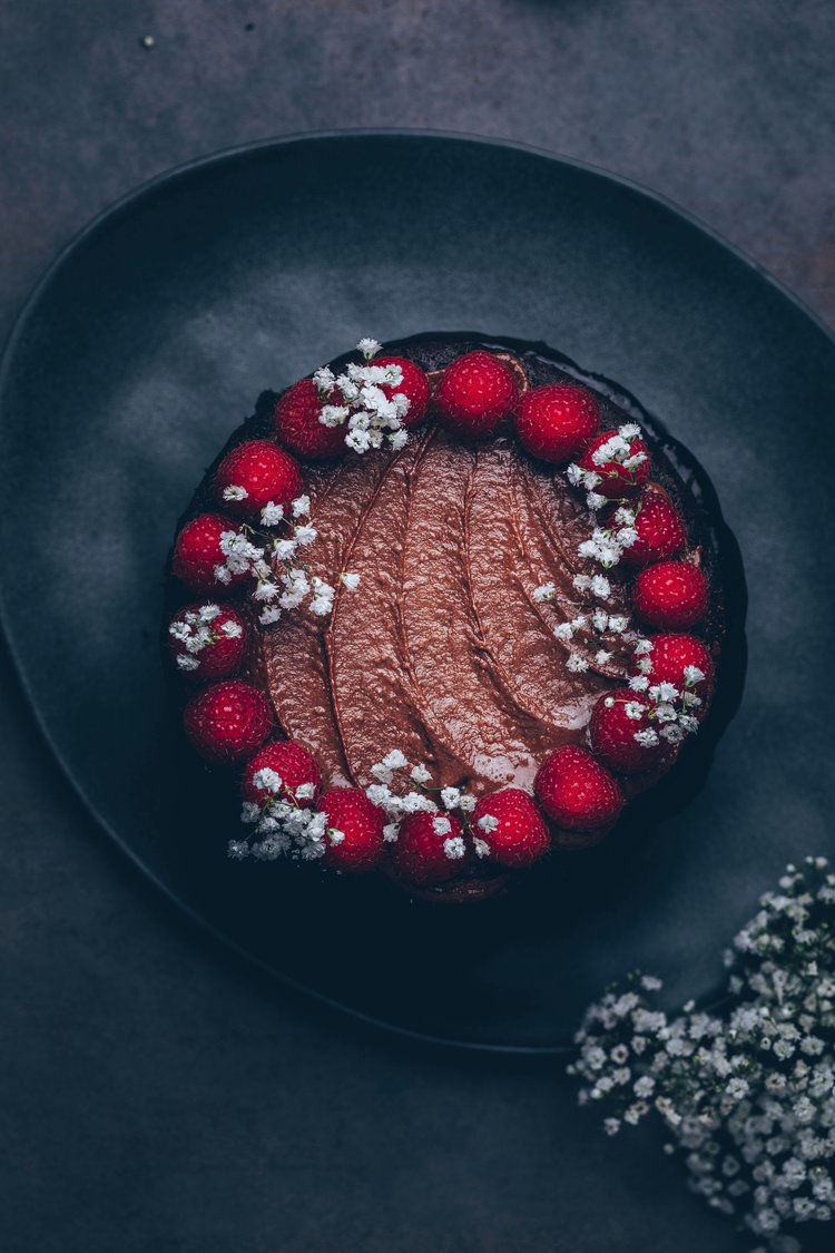Chocolate cake topped with raspberries and flowers