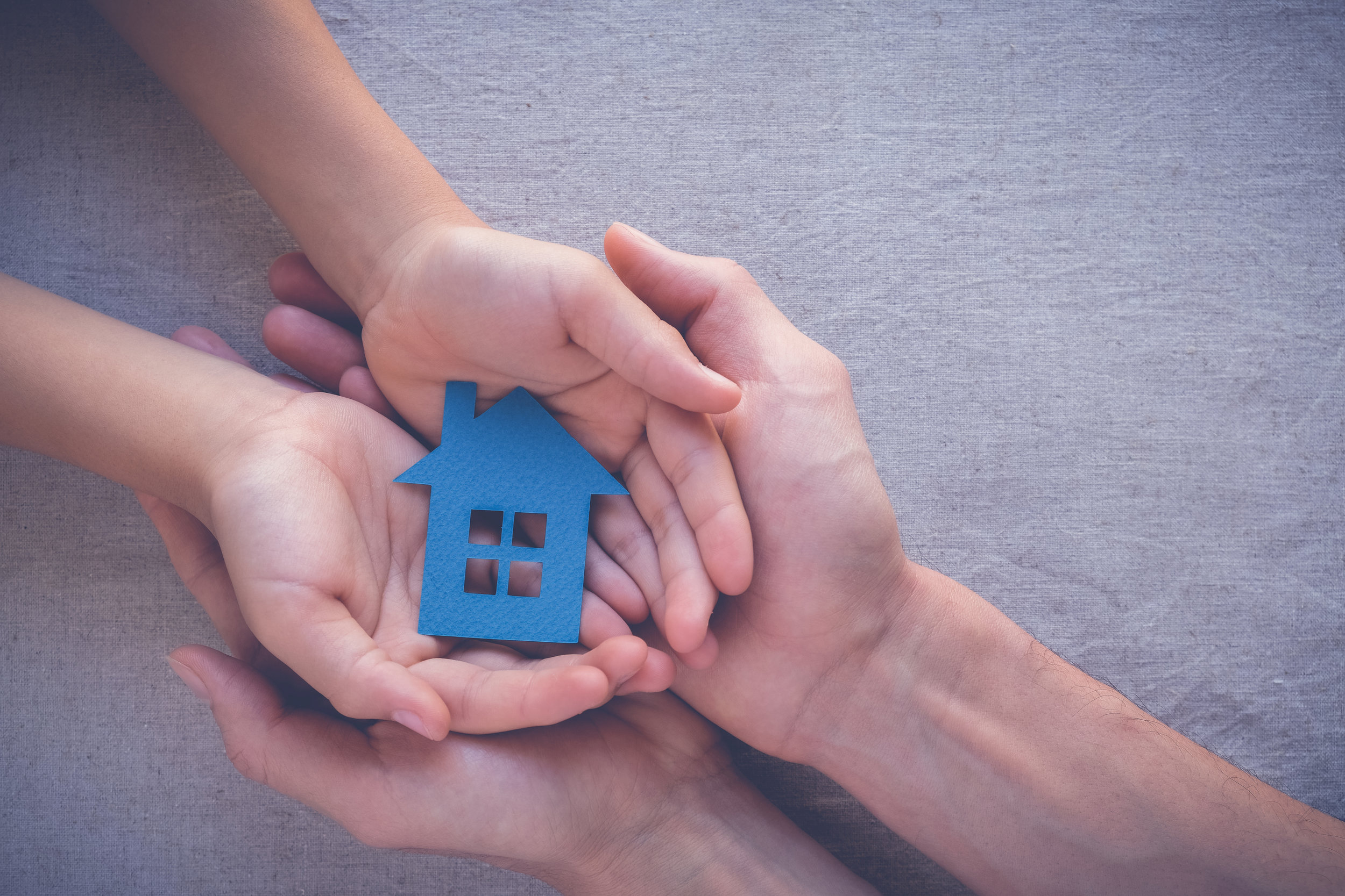 Hands holding a house