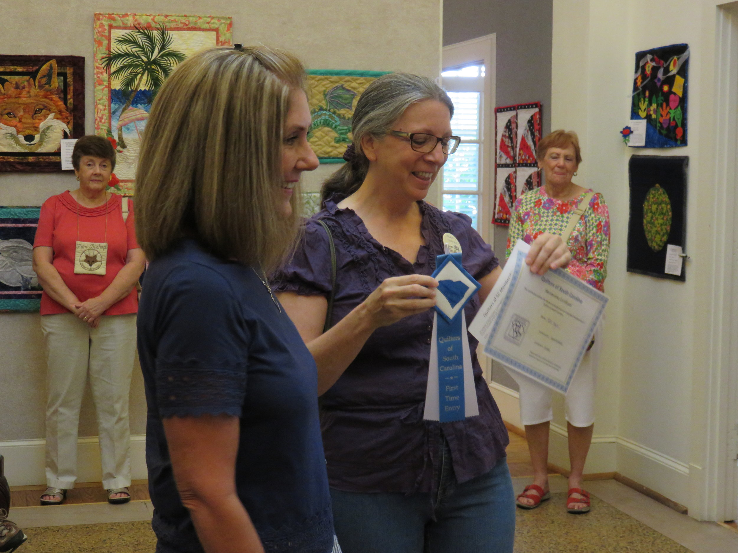 """Patti Hayes receives her ribbon and certificate from Karen Kirkland, president of the """"Quilters of South Carolina"""" state association."""