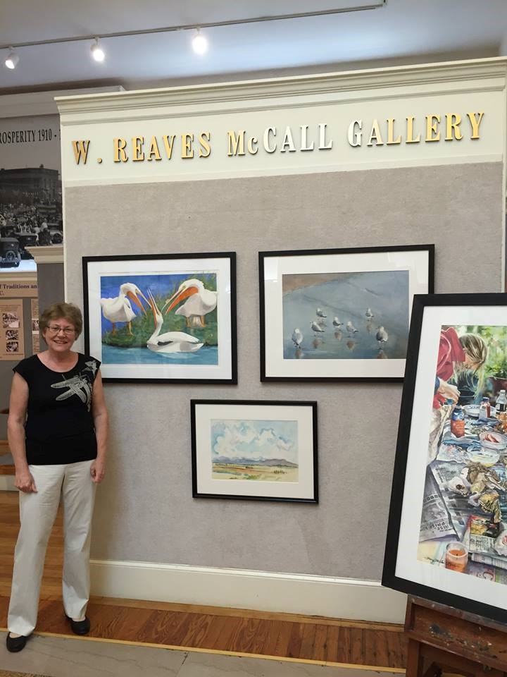 """Artist Barbara Rohde of Durham, NC stopped by the Hartsville Museum to observe her painting """"Gossip"""". This work is transparent watercolor on paper and received the Supporters of Artists (SOA) Award."""