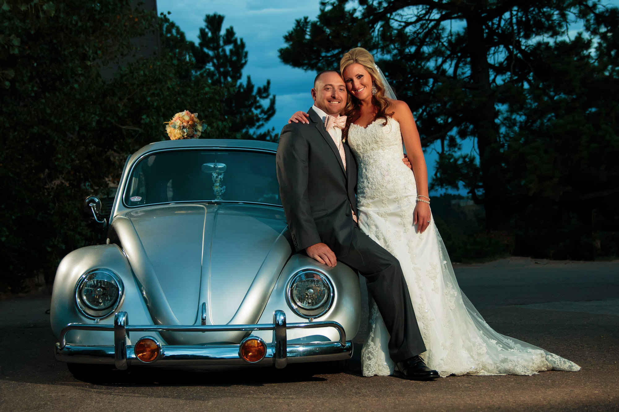 Bride and groom lounge next to a classic Volkwagen beetle during a mount vernon canyon club wedding