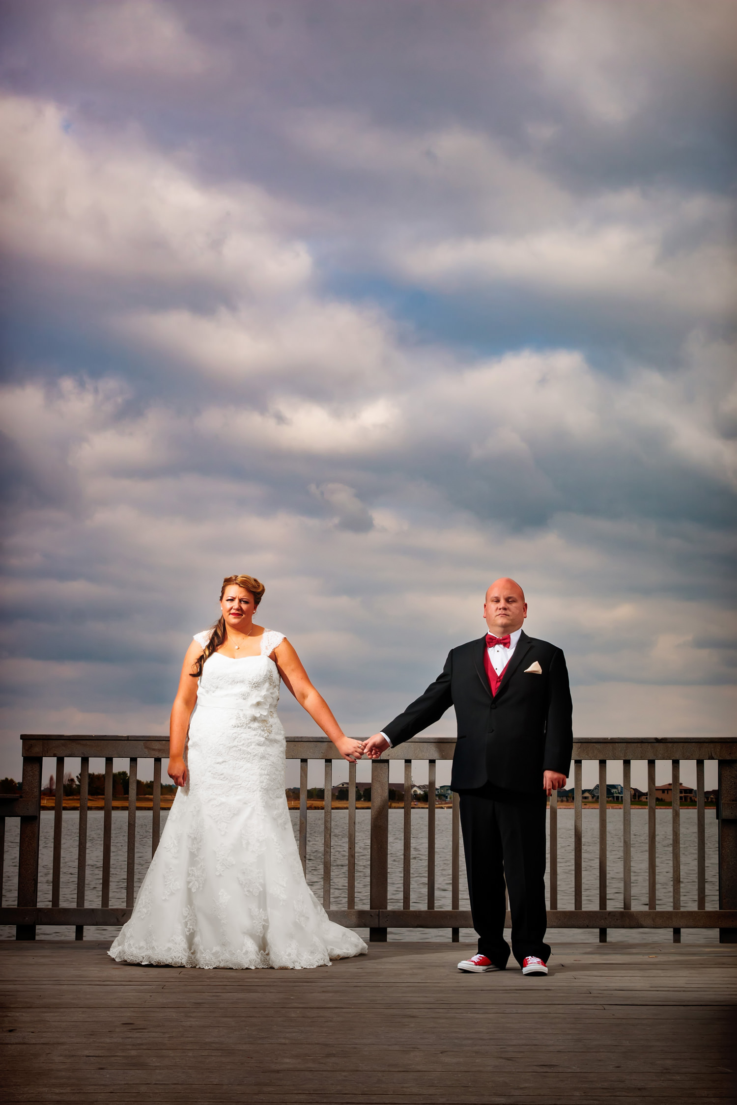 bride and groom relax in a down moment on a lake dock as capture by tomKphoto, windsong estate wedding photographer