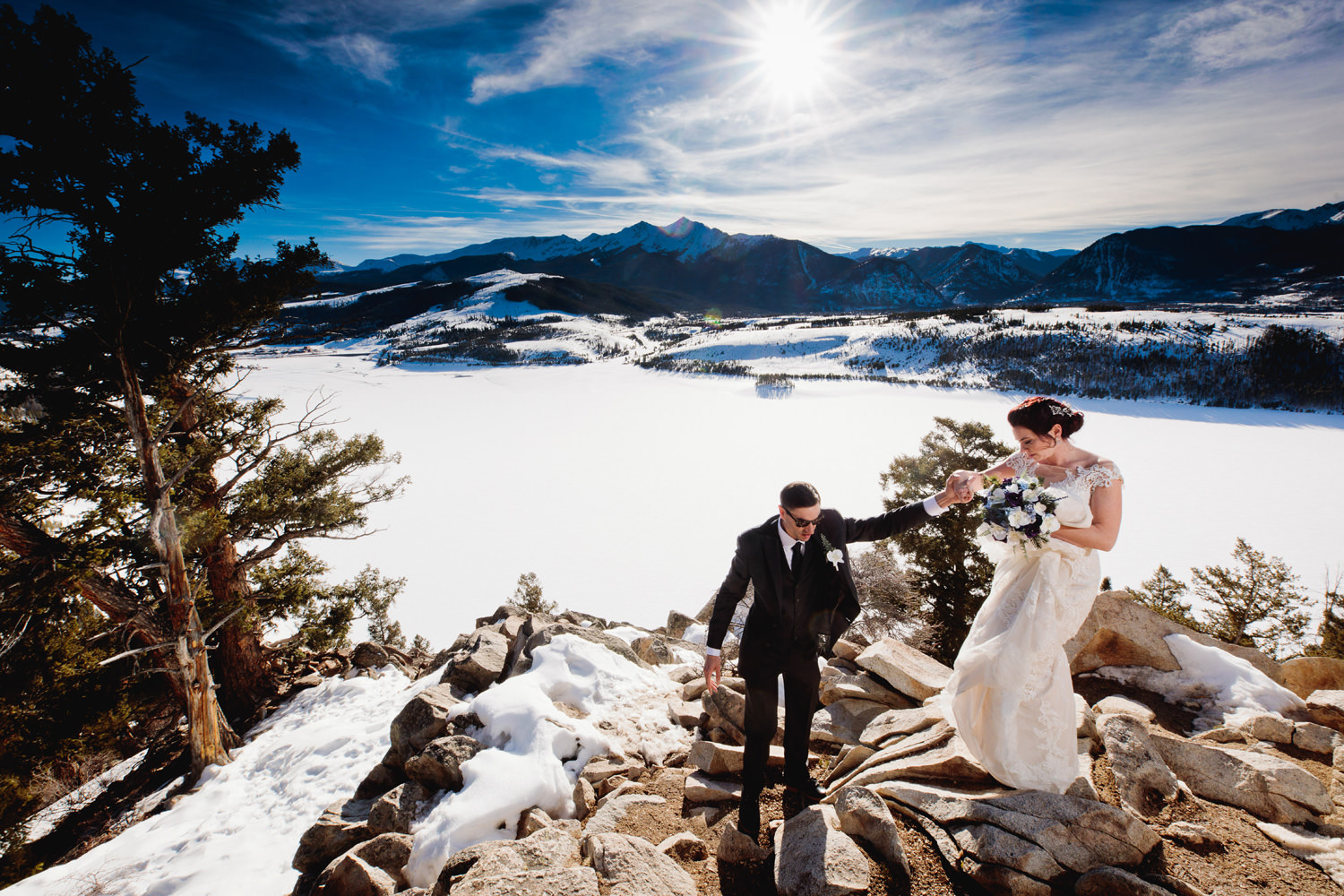 groom helps bride down rocky terrain captured by sapphire point wedding photographer tomKphoto