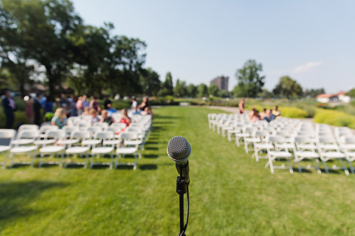 ceremony microphone sits alone on the lawn while guests are seated during a washington park boathouse wedding in denver, colorado