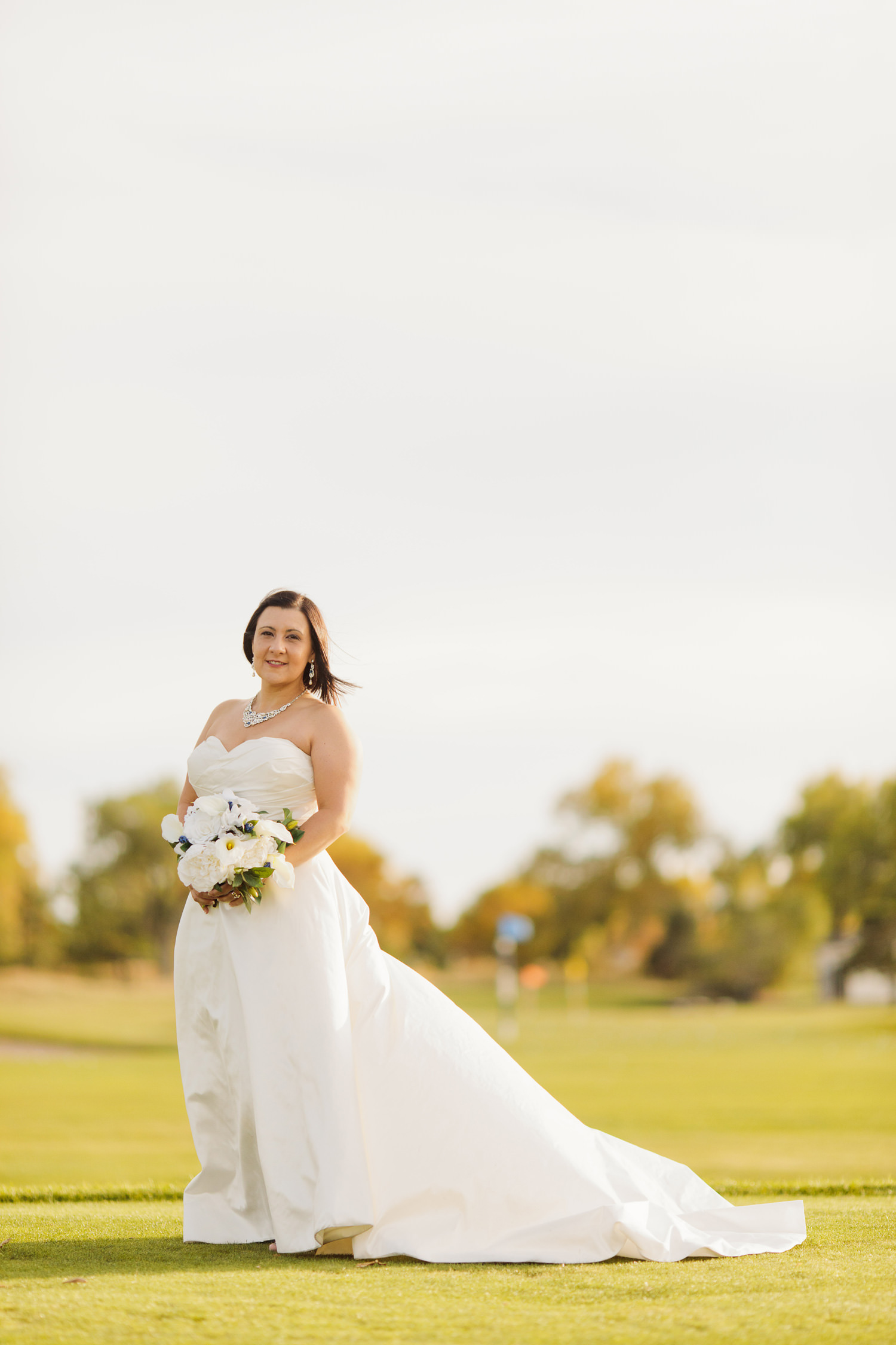 bride relaxes on golfing fairway during a Valley Contry Club wedding in Centennial, Colorado