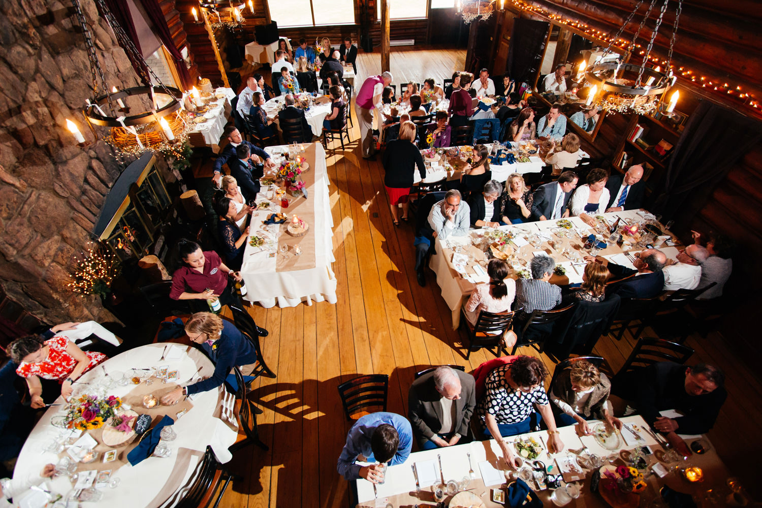 over 100 guests enjoy a reception feast during a twin owls steakhouse wedding in estes park, colorado