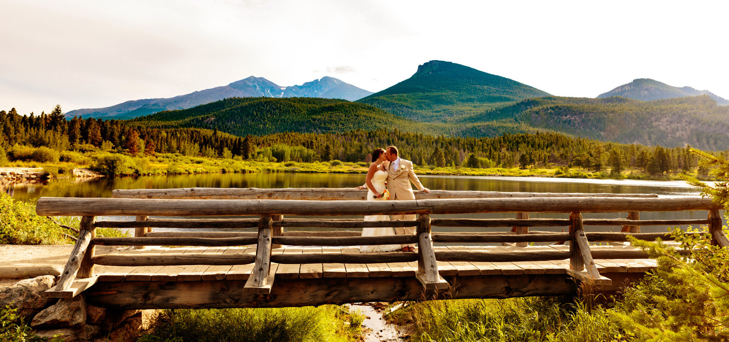 bride and groom relax on a wooden bridge at Lily Lake during a Taharaa Mountain Lodge wedding in Estes Park, Colorado