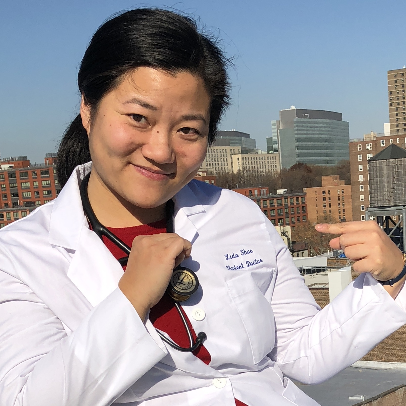 Image description: Lida, hair in a ponytail, wearing a white doctor's coat pointing to her name embroidered onto the chest, sitting in front of a city skyline.