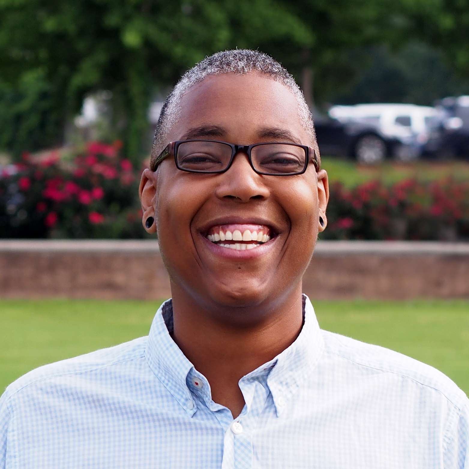 Image description: Sean is smiling at the camera in front of a green grass and flowers. Sean is wearing black framed glasses.