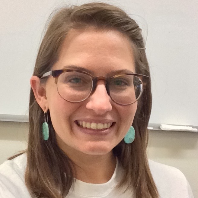 Image description: Carolyn is smiling at the camera in front of a whiteboard, wearing glasses and turquoise earrings.