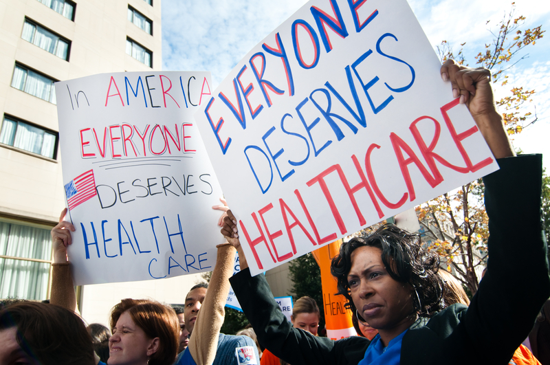 """Image description: Two women at a march holding up signs that read """"everyone deserves healthcare"""" in red white and blue."""