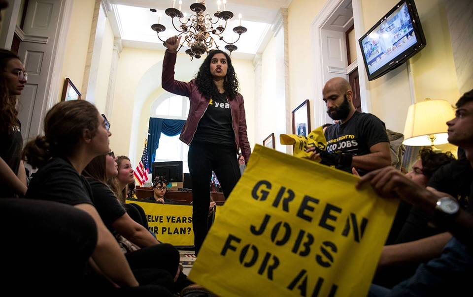 """[Image Description: A photo of a thin, olive-skinned and dark, curly haired female appearing person with her right fist raised. She is surrounded by a small group of people. One individual is holding yellow sign with green writing that reads, """"Green Jobs for All"""". Above the female appearing woman is a chandelier. To the right is a door with a television mounted on the wall. To the left is another door. Behind her is a window with blue curtains. The wall are yellow. ]"""