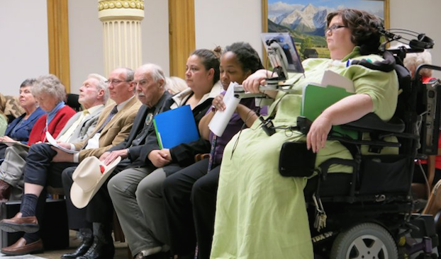 Image description: The late Carrie Ann Lucas, wearing a lime green dress, appears in court using her power wheelchair. Image credit: The Colorado Independent.