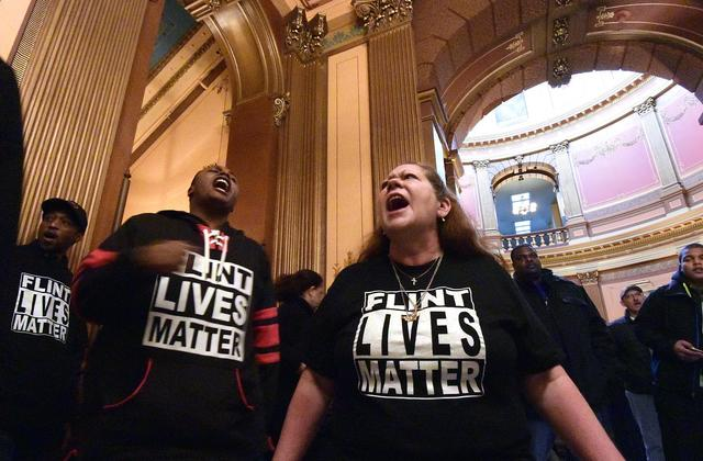 "Image Description: two individuals protesting in black t-shirts that say ""FLINT LIVES MATTER""."