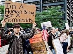 A man with brown skin and a brown cap wearing a striped button down shirt holds a sign written on cardboard which says: I'm A Human Being Not A Commodity. Behind him are other protesters with signs and an urban high rise building.