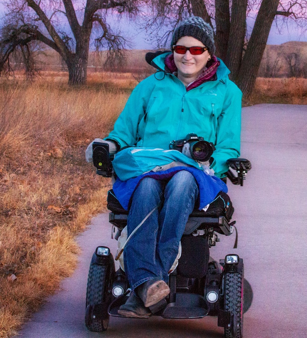 Image description: Kim, smiling and looking at the camera, wearing a light blue jacket and jeans, and holding a camera in her lap. Kim is seated in a power wheelchair on a concrete path, with tan grass and cottonwood trees in the background.