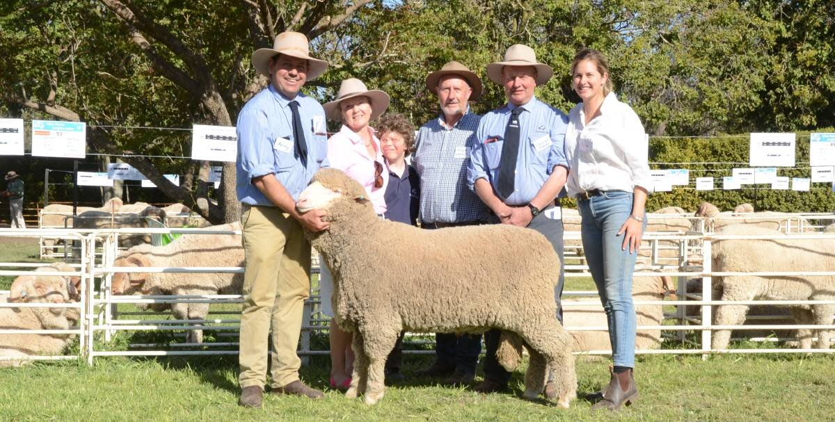 HR stud manager Andy Maclean holds the $4000 Poll Merino draft-topper of three averaging $3500 purchased by Edwina Savage, Pine Grove, Canowindra, with Eddie and Hugh Savage, HR principal, George Falkiner and daughter, Olivia.