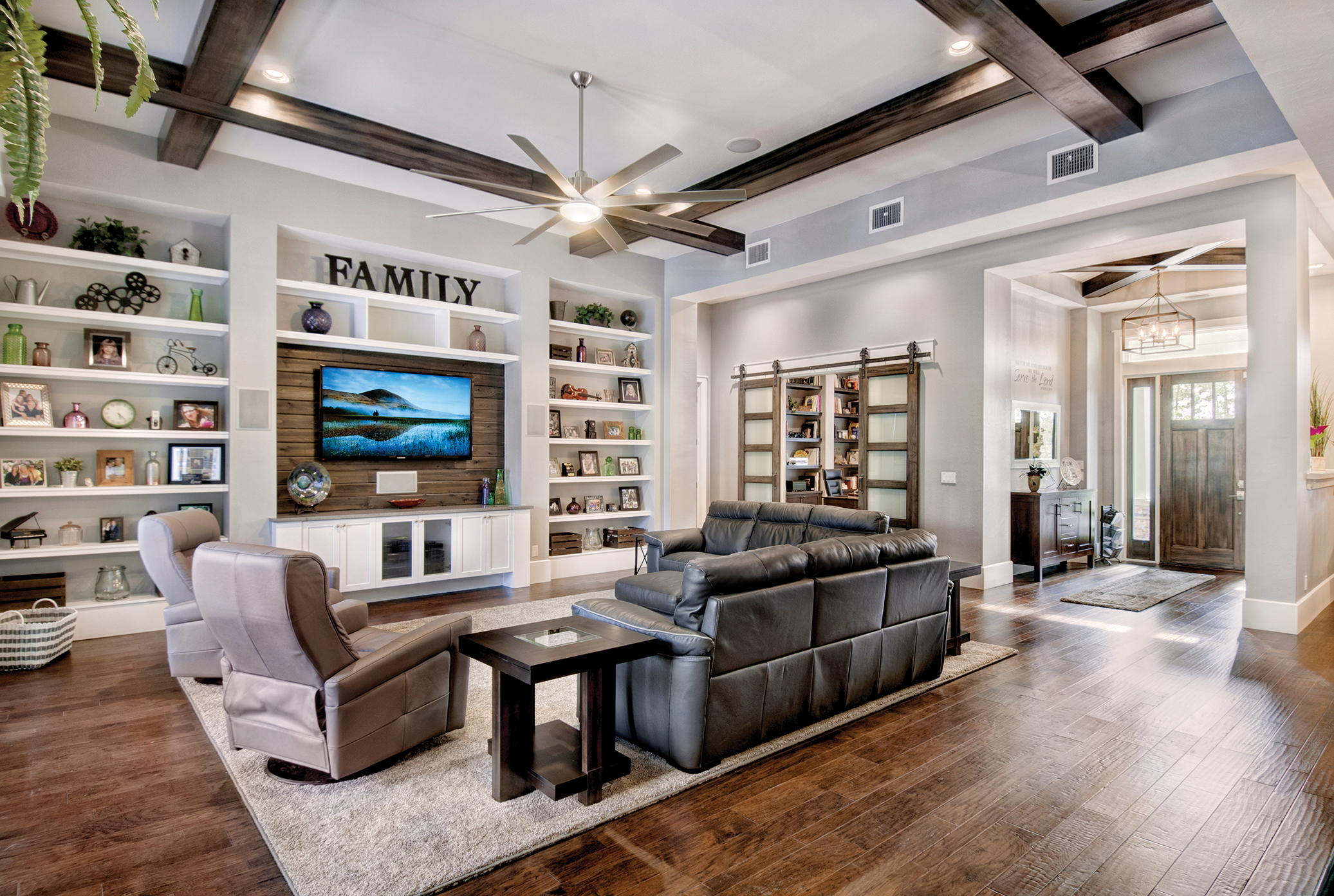 """The focal point of the comfortable great room is a set of built-ins with a repurposed wood accent. """"We were able to take some of the leftover wood from the ceilings on the lanai and use it in the great room,"""" says Sater. """"It's so much better to look for creative alternatives than to throw something out."""" Under beams that match the grids in the windows, leather sleeper sofas are both comfortable and practical and act as overflow sleeping areas for guests. On the other end of the great room is the office, strategically placed so Sater isn't totally isolated from the rest of the house as he works. If more privacy is needed, modern barn style doors can be closed. """"While the outside of the house is traditional, my wife found she liked a more transitional look inside. It's a great combination of new and old,"""" Sater explains."""