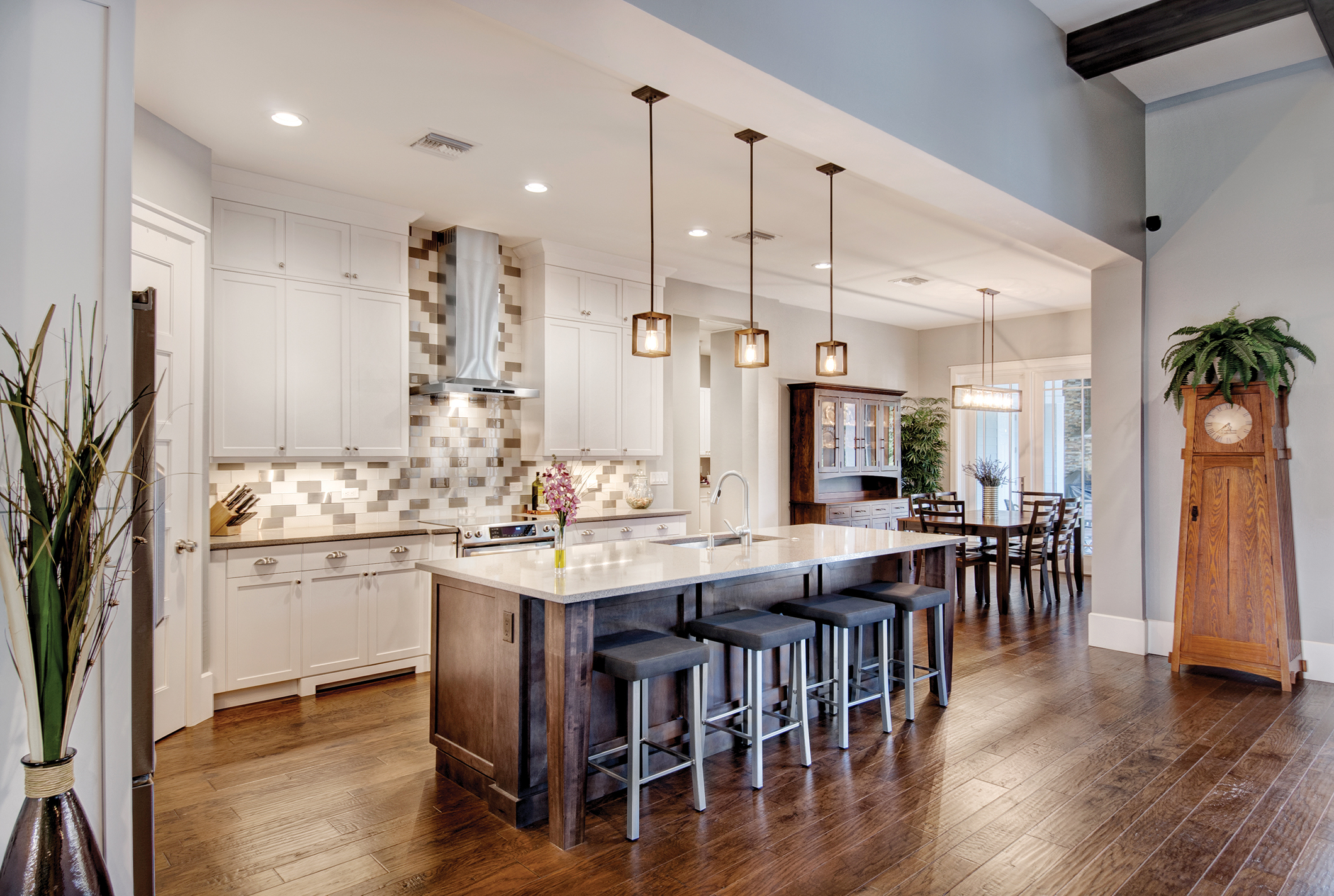 """The great room flows directly into the airy kitchen. Shaker-style cabinetry is set against a subway tile backsplash with metallic accent tiles. A modern stainless steel hood and Edison bulb lights are a perfect example of how modern and traditional elements blend seamlessly in this home. In the nook, a handmade Amish hutch was custom built for the space by the Millers in Sarasota. """"We were familiar with the family who made the piece because of our time in Amish country in Ohio. They make such high-quality furniture pieces that it's an instant heirloom. We commissioned them to make a few pieces throughout the home."""""""