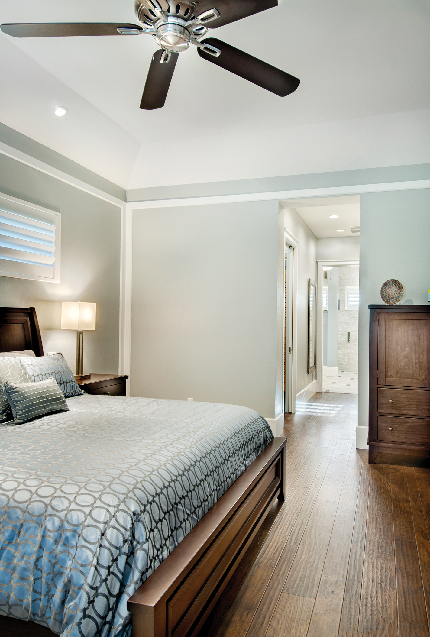 """The master suite is tranquil with shades of soft blue. """"We wanted to keep this room simple and comfortable,"""" says Sater. Through the hall, the master bath sports more of the beautifully stained woods found throughout the home."""