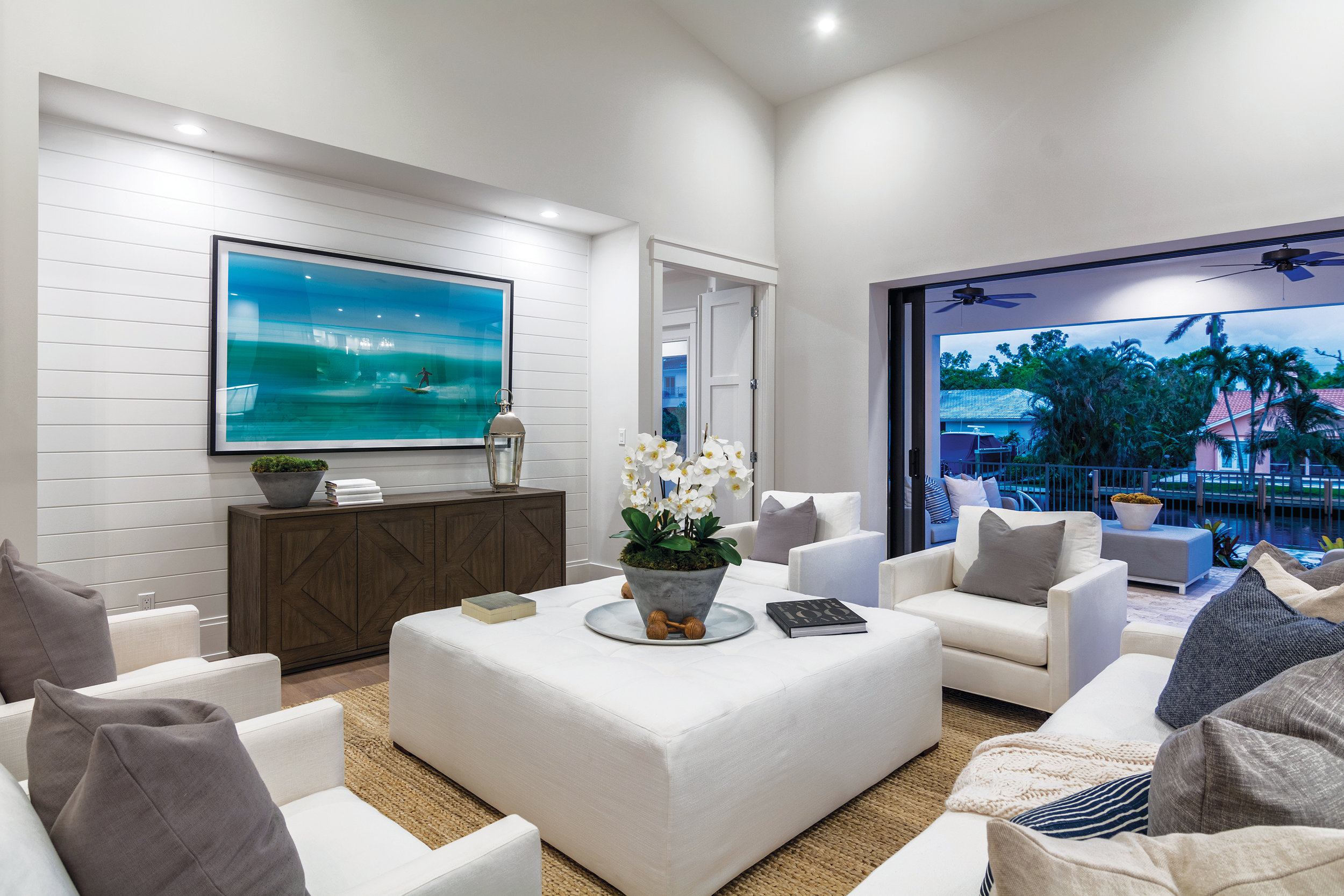 Special details like the shiplap in the recessed media area create a coastal feel that fits the home's location in Aqualane Shores.