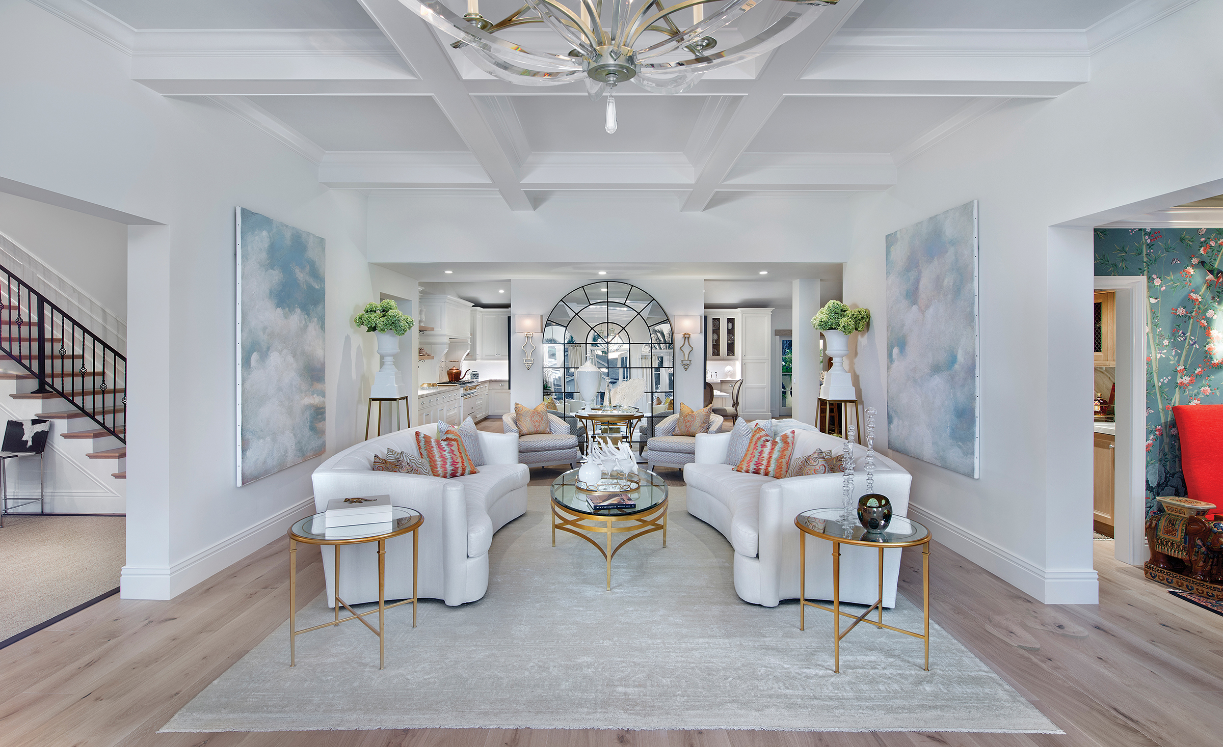 """This home was about surprise elements for me—from the way a hallway would open into an intimate sitting room, to accent items found throughout, I wanted people to be excited about each new space—,"" says August. An expertly curated mix of traditional formality and a relaxed lifestyle is apparent. The sleek silhouette of twin Maison sofas pairs with the gold finish of the coffee and side tables offering an '80s vibe. The art in this room is from August's Wendover collection, inspired by her love of Florida's always beautiful sky. The large antique mirror was retrofitted for the home and plays off the arched windows it reflects."