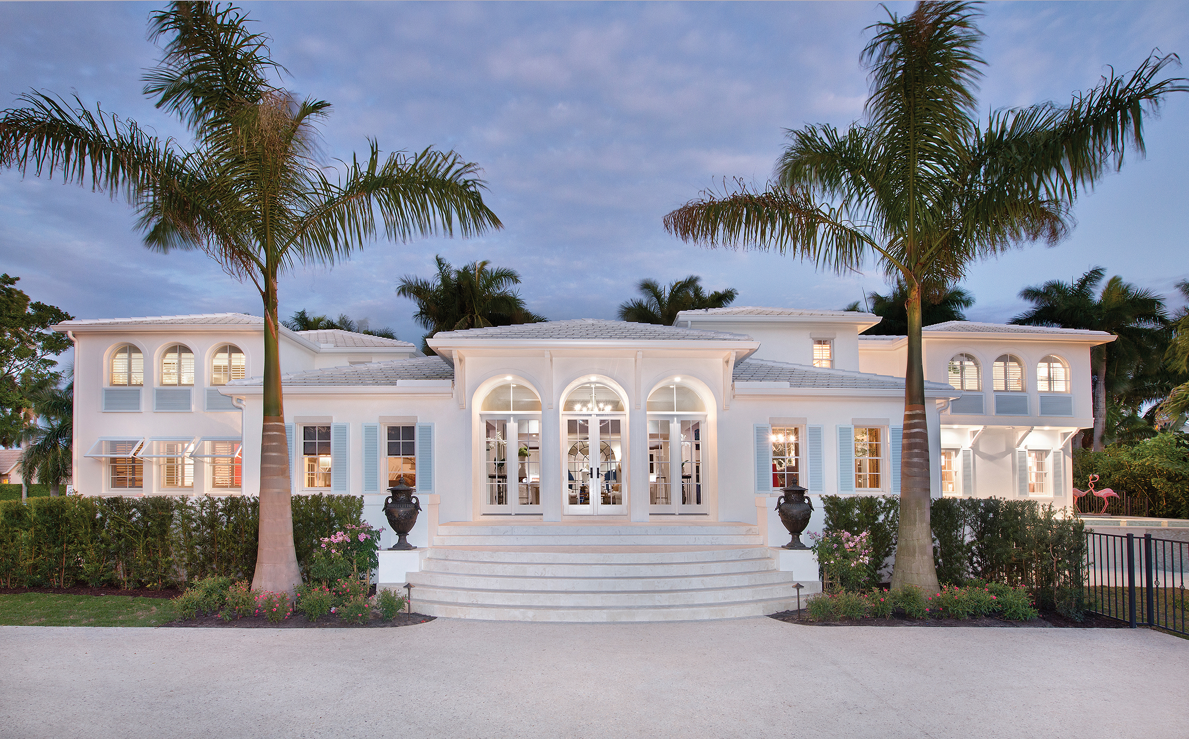 "As the Bermuda-style home is viewed from the new custom-poured shell driveway one would never guess at the extensive redesign and artfully executed renovation which took place. The orientation of the home was changed from the narrow side street to face Gulf Shore Boulevard, a second two-story wing was added on the right, and the triple-arches were changed to reveal a new grand entryway. ""It took a lot of structural re-engineering, but I'm glad we were able to add the arches because they look spectacular as you approach the house,"" notes builder Jay Bowerman."