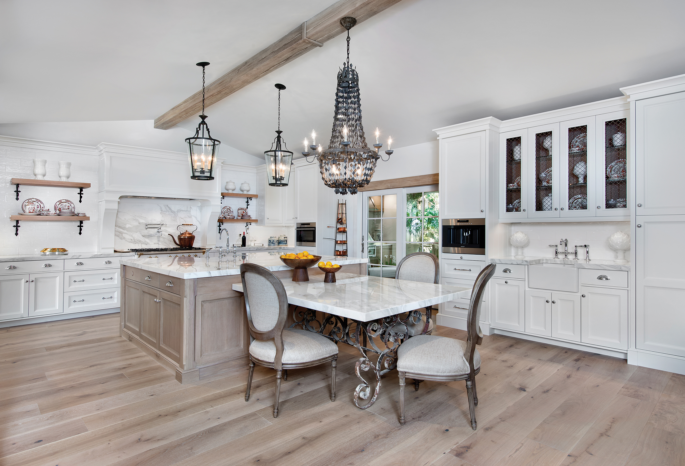 The French country kitchen is consistently one of the favorite rooms in the home. Designed by Carol Ruffino and manufactured by Ruffino Cabinetry, the Alabaster White-finished cabinets provide the perfect canvas on which to build. Wire-grill door inserts with limed oak T&G backs, and shelves with custom iron brackets complement the beautiful limed oak island. Ruffino's design incorporated a Lacanche Chassagne Classic Art Culinaire French range. Williams used the French pastry table at the end of the island to enhance the classic European look. Calcutta Gold marble and French white oak flooring complete the space.