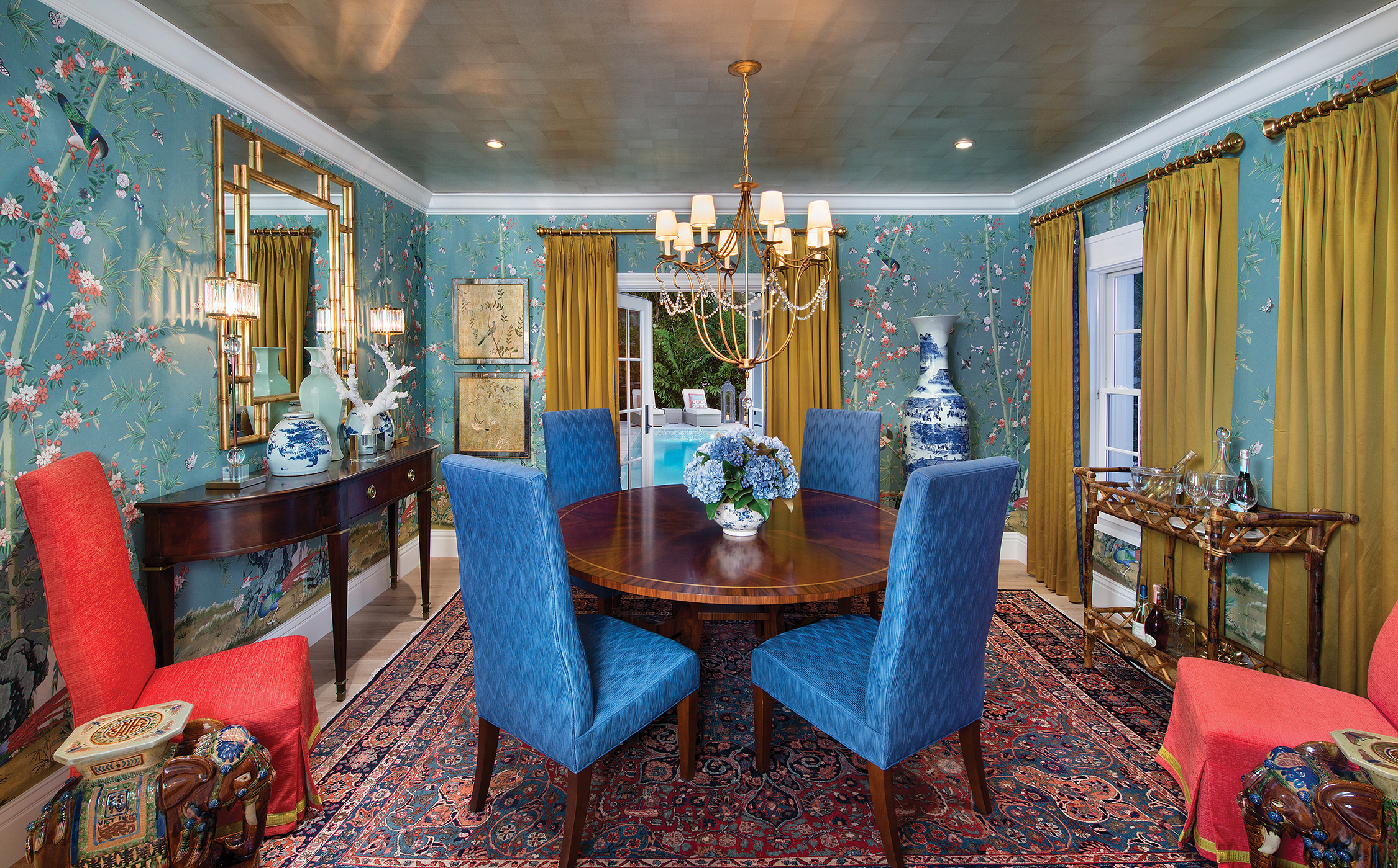 Filled with saturated color and textural layers, the dining room is a space that gives the homeowners a truly formal entertaining area. American made chinoiserie wallpaper represents a new opportunity for designers as it replaces the more expensive and labor-intensive hand-painted method. The wallpaper sets the color scheme and period for the room, and is accented with the punch of Chinese red and oversized porcelains. The dark wood dining table sits on a rug that reinforces the traditional feel.